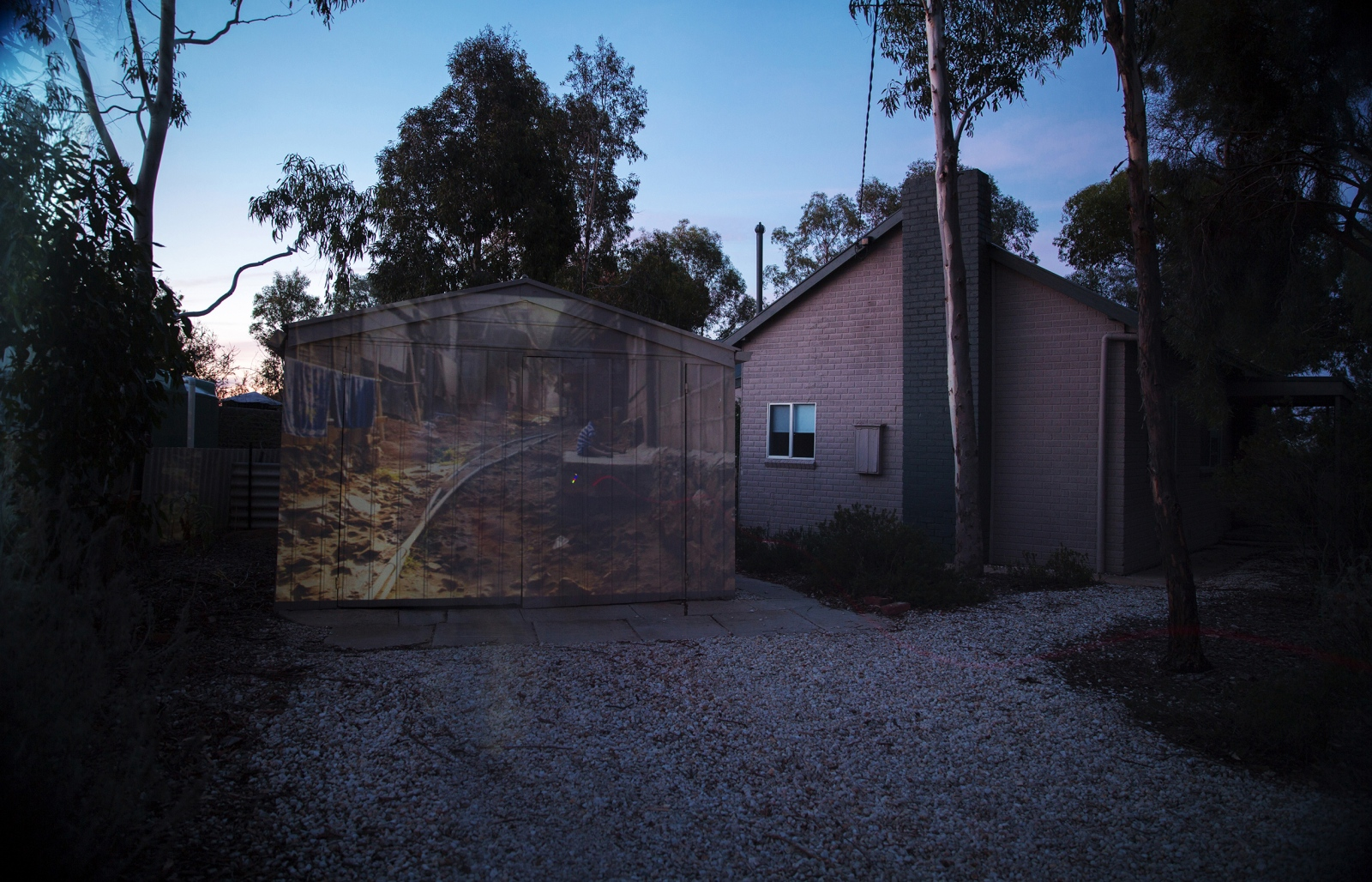 A projection of a young boy in Tham Hin refugee camp on the Thai Burma Border projected onto a home where a family from Yangon now resides in rural Victoria, Australia.  VICTORIA, AUSTRALIA, 2016.