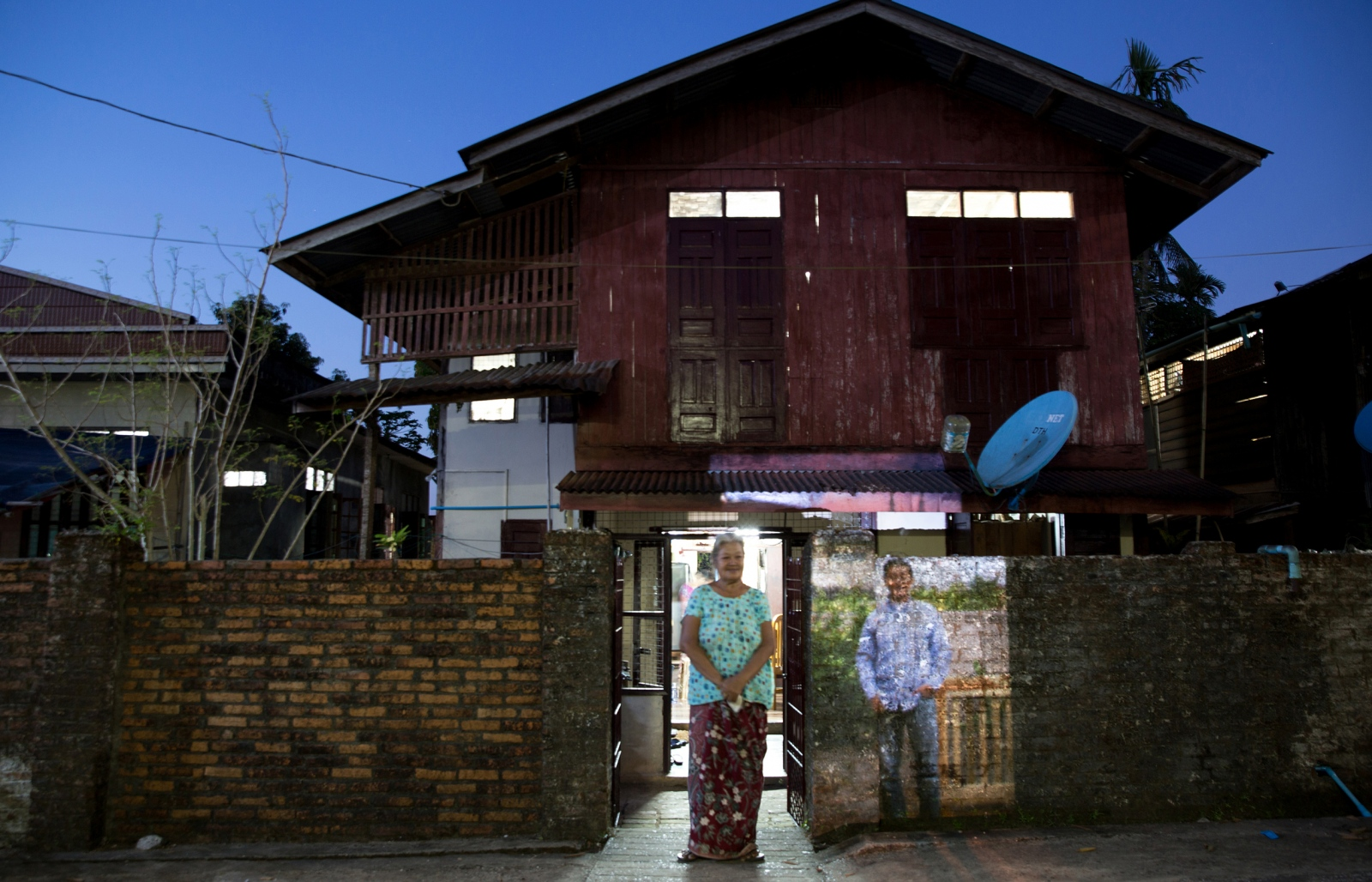 A woman in Mawlamyine, Burma (Myanmar) stands by a projection of her son who has resettled in Victoria, Melbourne.  MAWLAMYINE, BURMA (MYANMAR) – November 2015.