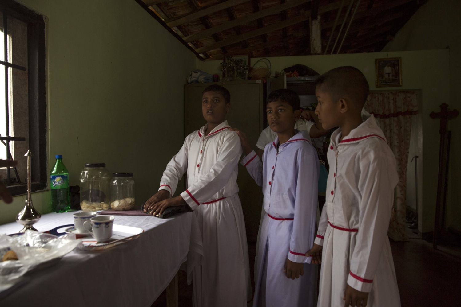 Jeewana Shehan, 13, (left) helping as an alter boy at the Roman Catholic church in Sirambadiya village. His mother is Afro-Sri Lankan but his father is Sinhalese and has lost his African appearance.
