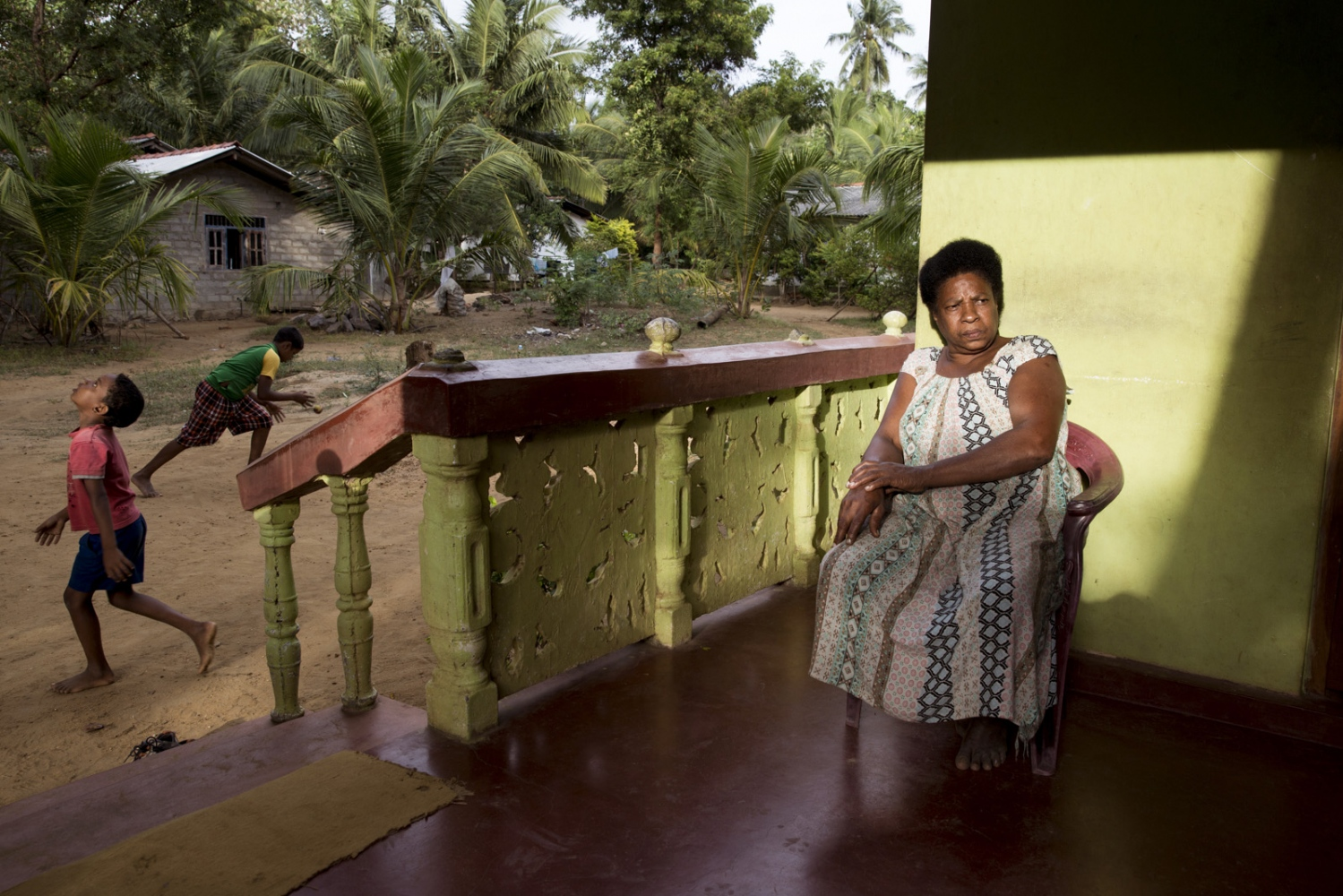 Mary Janet, 55, sits on the porch of a neighbours house in the village of Sirambadiya.