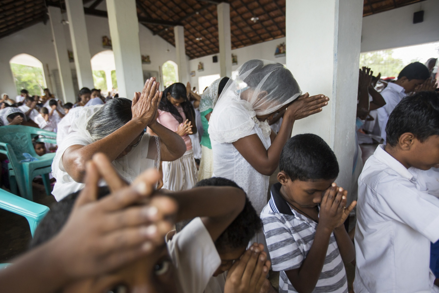 Villagers pray during Sunday morning mass at Sirambadiya Roman Catholic church.