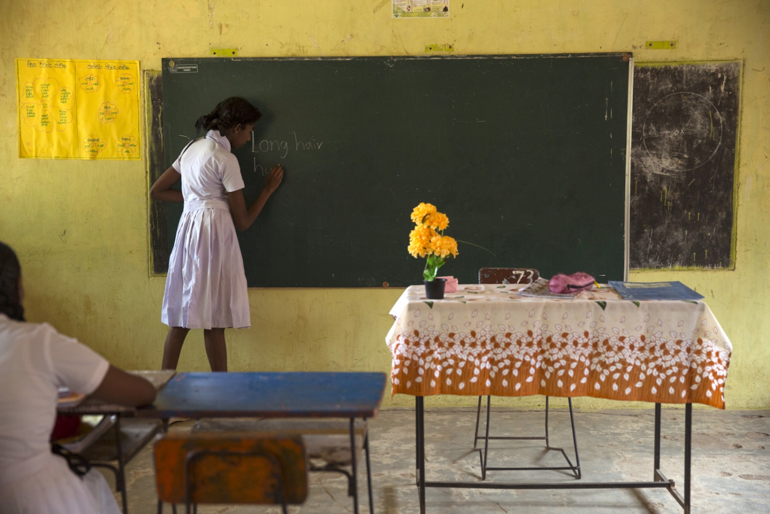 Afro-Sri Lankan Olivia Alexander, 14, practises writing english on the black-board at Sirambadiya school.
