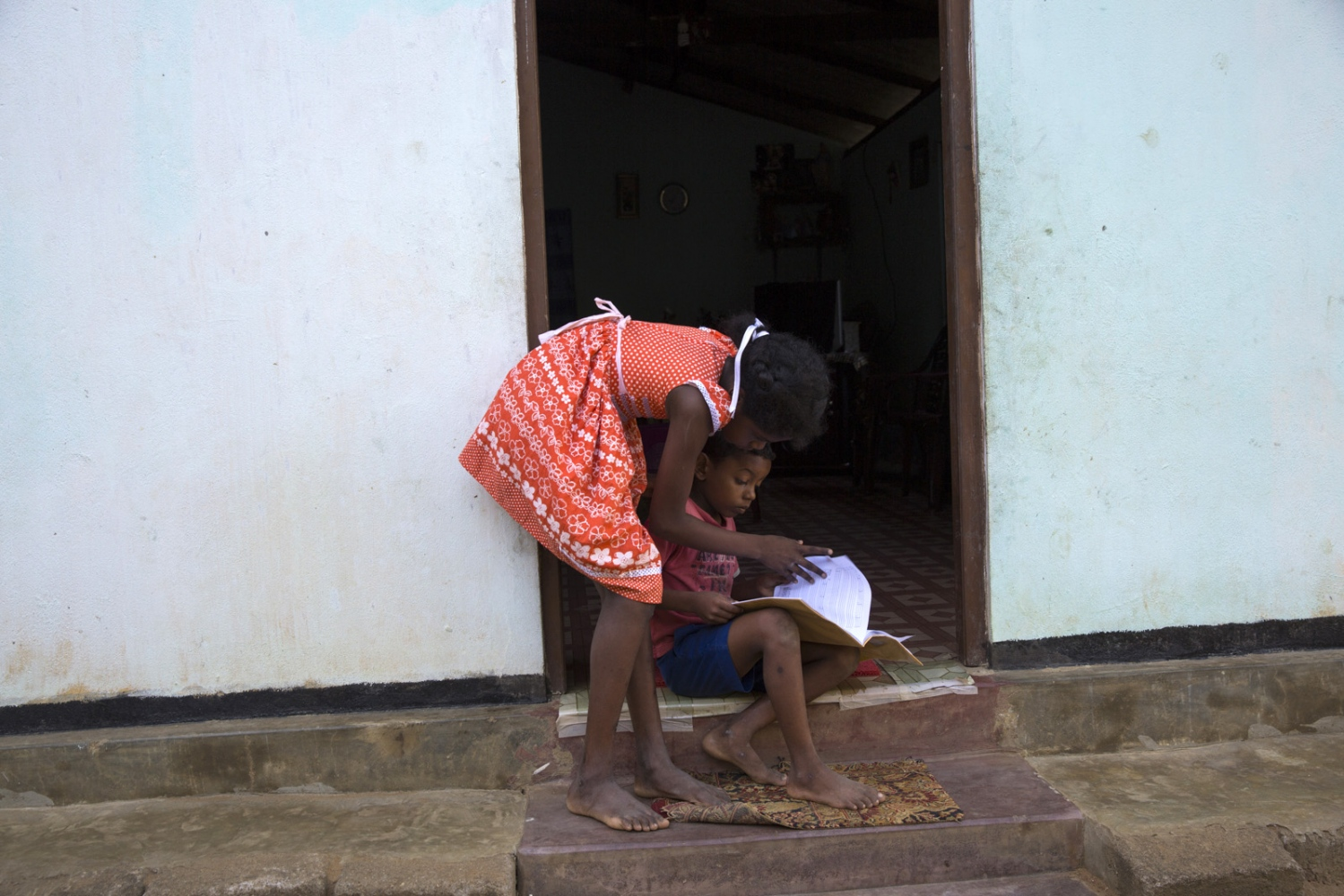 Warnakulasuriya Pravin Madushan, 10, helps her little brother do homework at home.