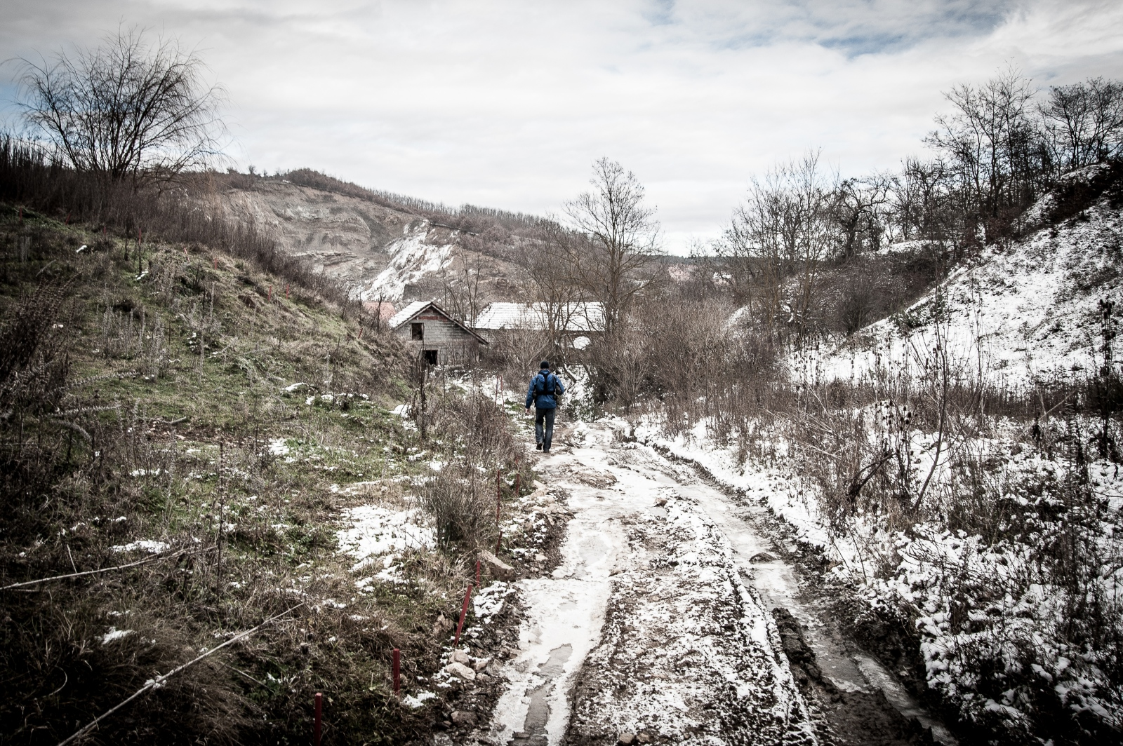 A de-miner searches along a snowy road returning to his village in northwestern Kosovo. December 2016.
