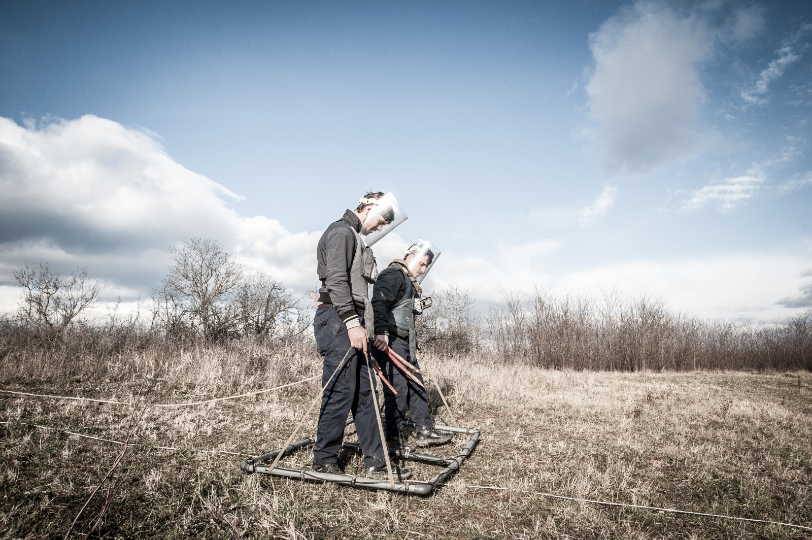 Two workers sweep a field near the village of Kryshec, where eleven cluster bombs were found and deactivated since August. December 2016.
