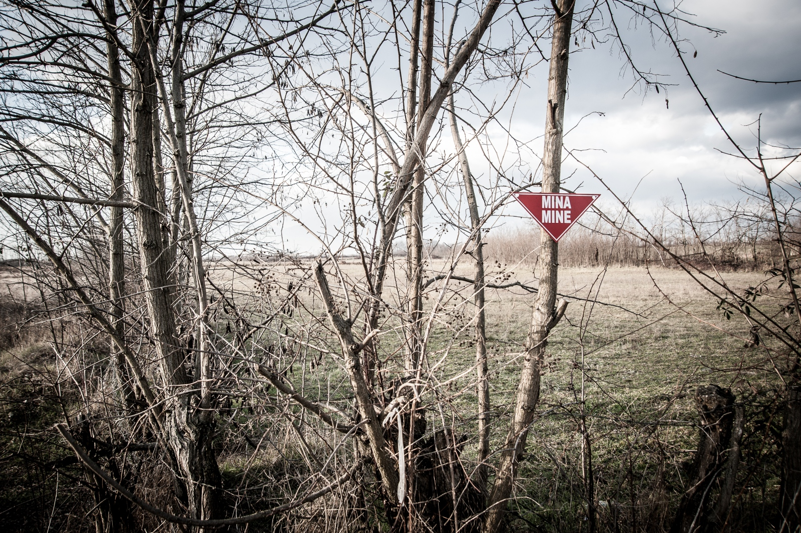 A sign indicates the landmine presence among the fields. December 2016.