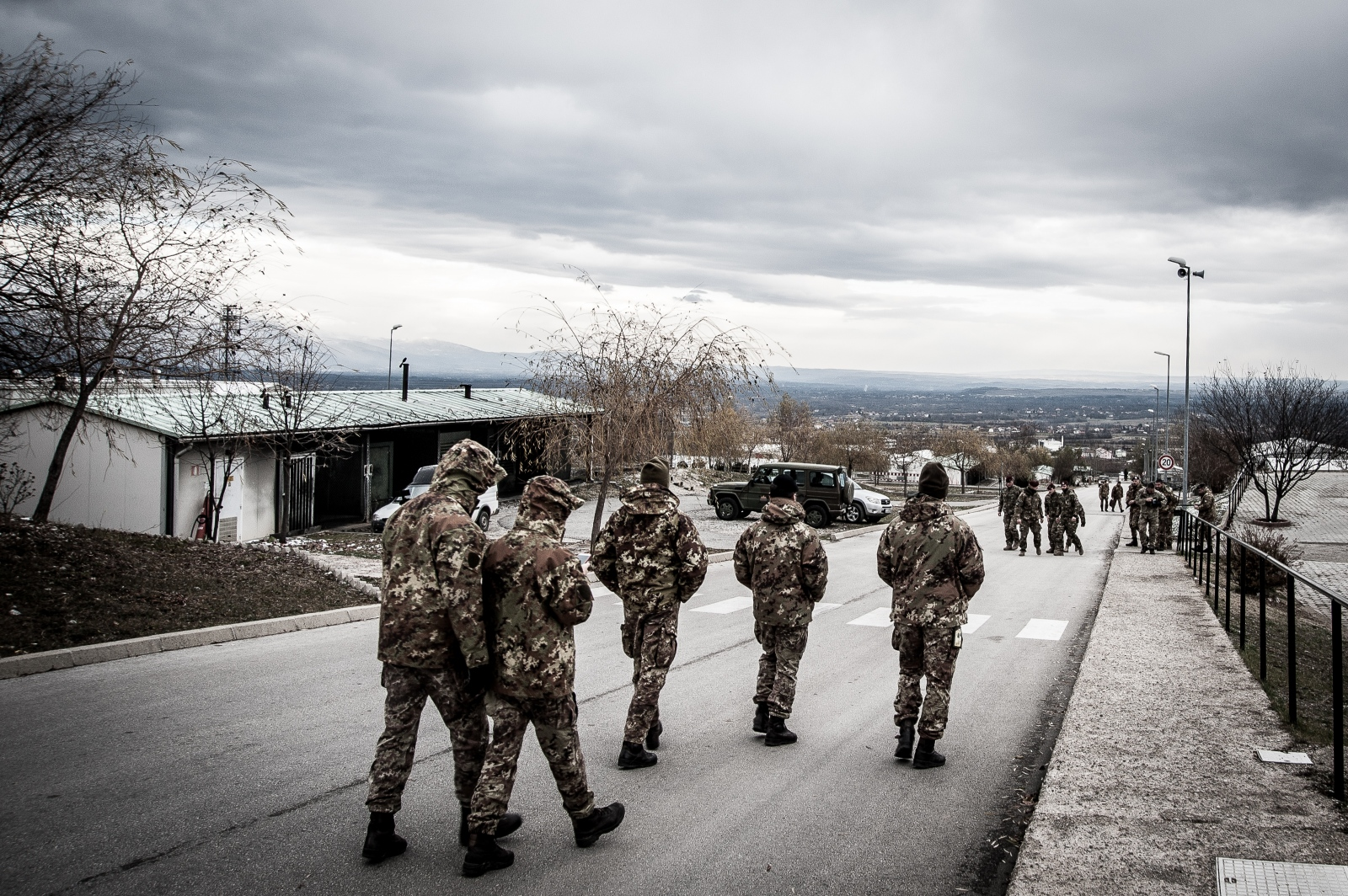"KFOR soldiers walk in the streets of Camp ""Villaggio Italia"" during a break. The Multinational Battle Group West is made up of about 5,000 soldiers coming from Italy, Austria, Slovenia and Moldova. The surveillance of the monastery remained one of the main activities performed by the Multinational Battle Group West in Kosovo."