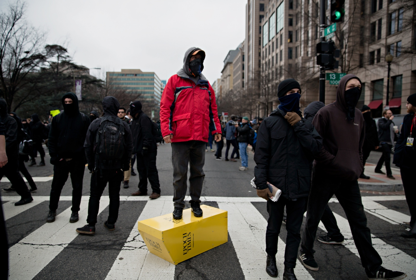 January 20, 2017 - Washington, DC, United States: An anti-trump protestor steps on a broken newspaper dispenser and cheers the crowd on. Various groups descended upon the DC area to voice their protest against Donald Trump's presidency they believed to have been stolen. The member of the Black Bloc broke windows of specific businesses such as the Bank of America, Chase Bank, some hotels and several bus station and ended with the destruction of a limousine.