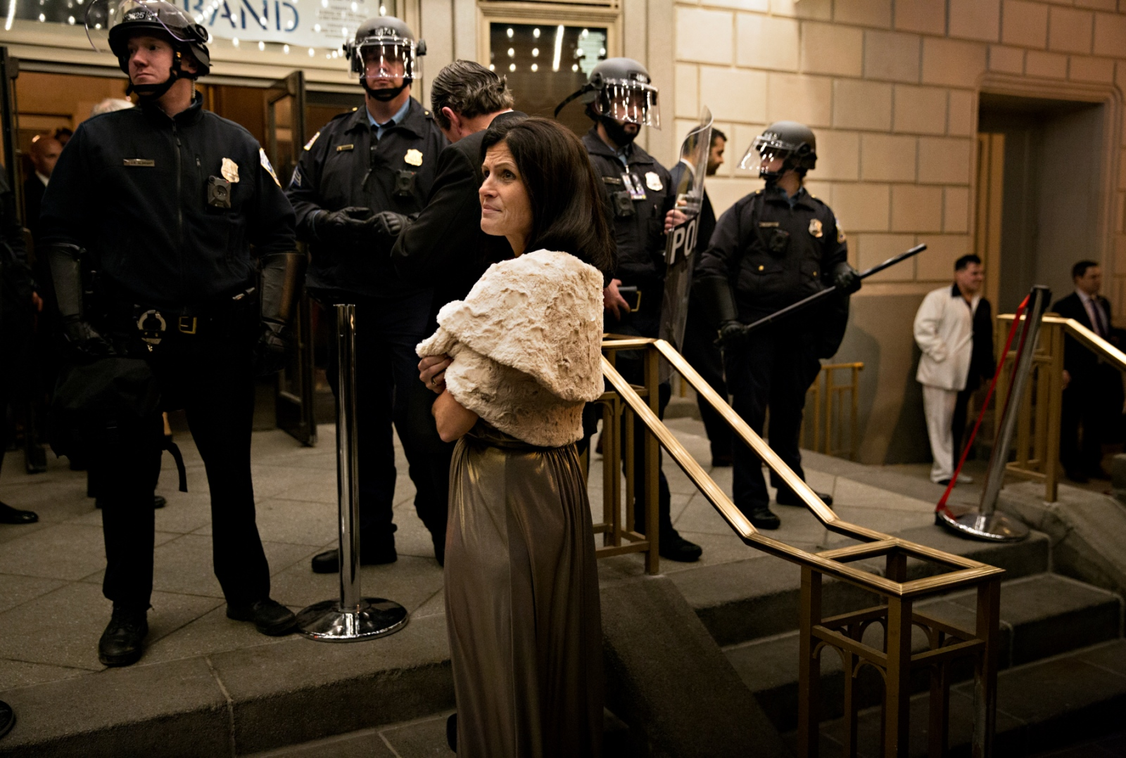 January 19, 2017 - Washington, DC, United States: A woman attending a Ball waits to be allowed inside and beyond the Washington DC police in riot gear.