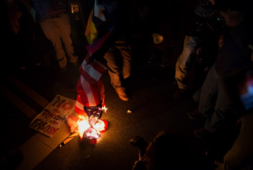 January 19, 2017 - Washington, DC, United States: Anti-Trump protestors set a US Flag on fire in front of the National Press Club.