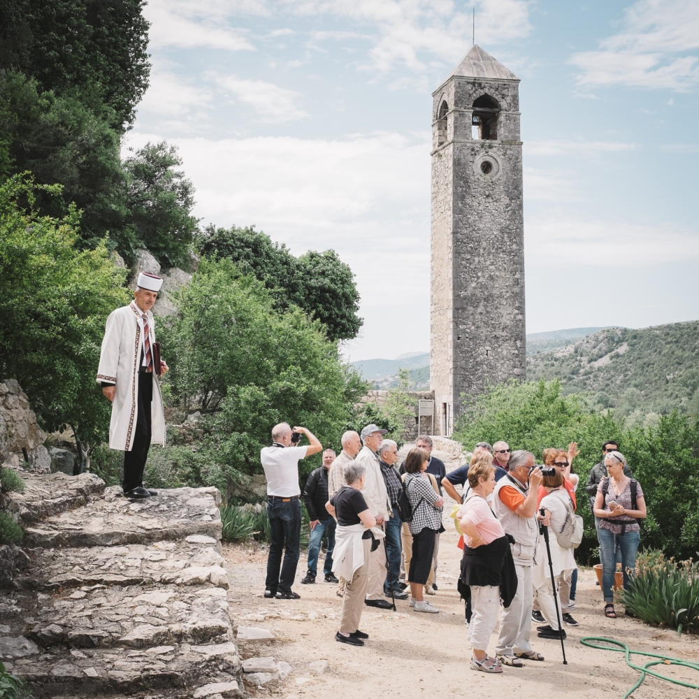 The imam welcomes tourists visiting Počitelj. Especially during the summer, the country is overrun by visitors from around the world.