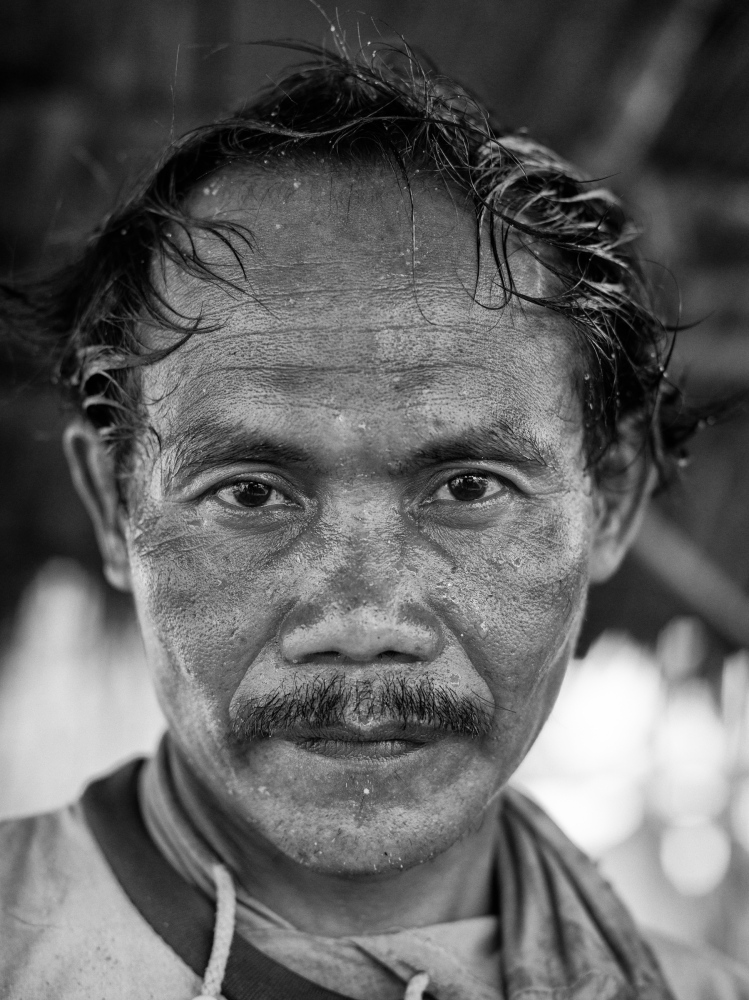 Paino, a 38 year old illegal tin miner from Lampung in Sumatra takes pose for a portrait on a pontoon near Rebo Beach, Bangka Island, Indonesia on May 6, 2016. Paino, has worked in tin mining industry as a minier for 15 years.