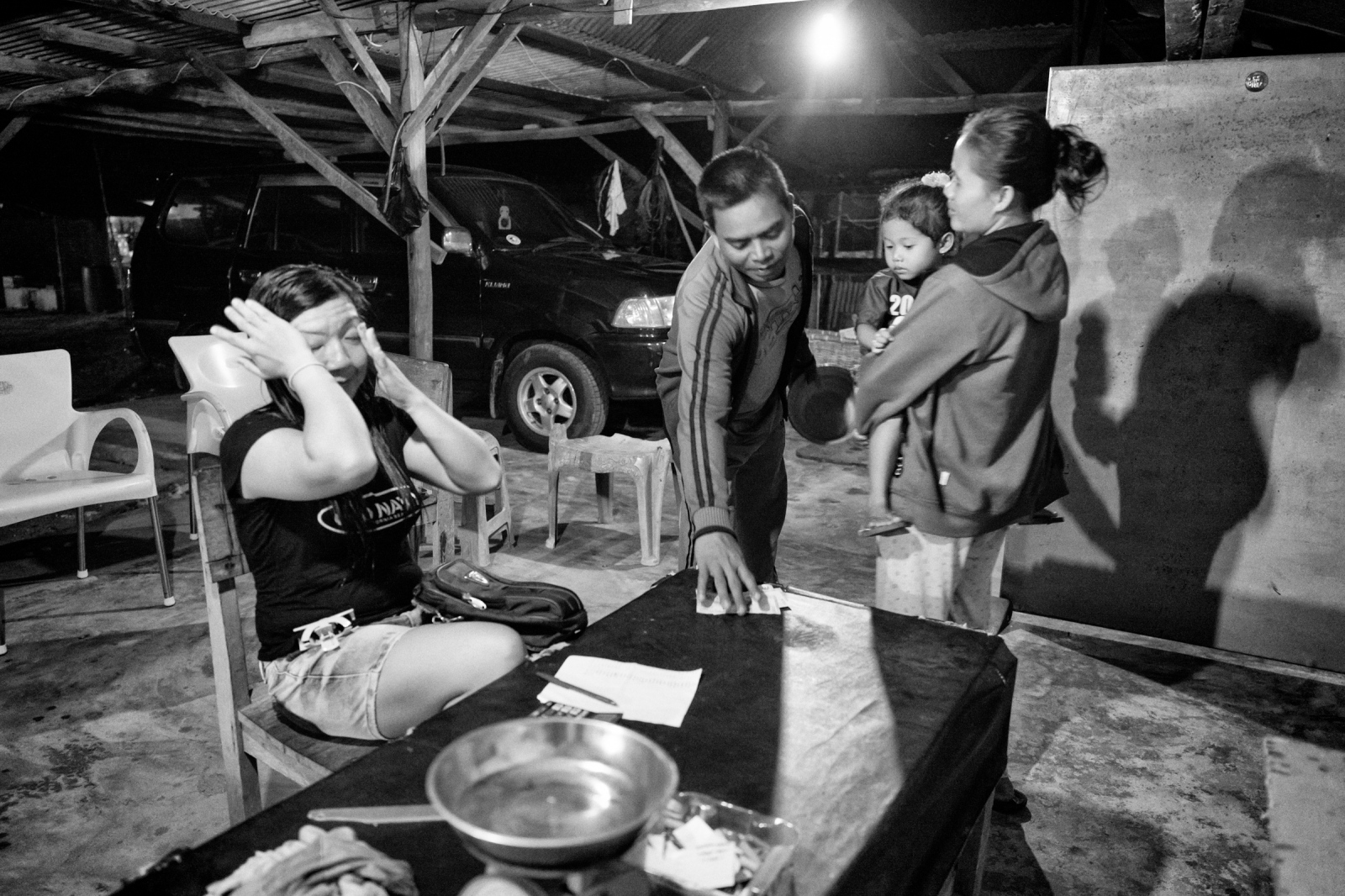 Local family gets money for selling tin to an illegal dealer at her house in Deniang village in Bangka Island, Indonesia on May 9, 2016.