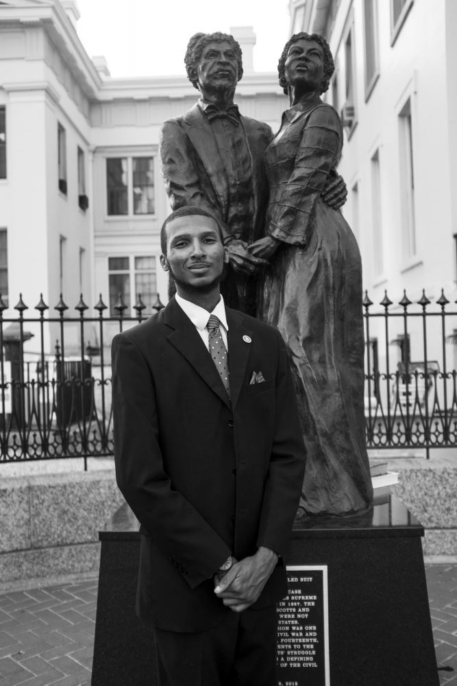 Farrakhan Shegog proudly stands next to his inspiration: a sculpture of Dred and Harriet Scott in front of the Old Courthouse.