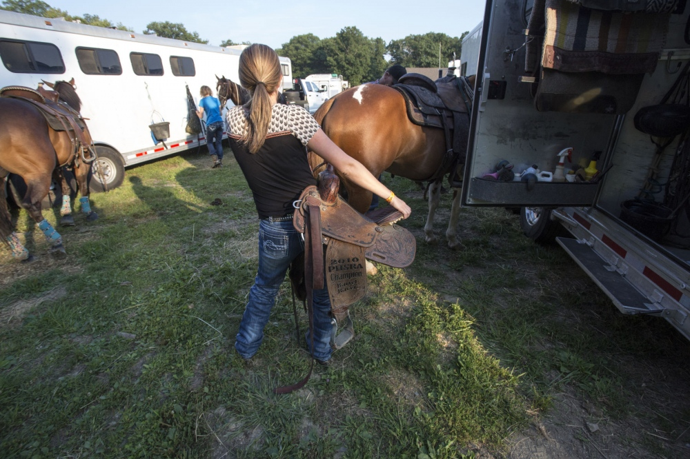 Taylor Young carrying her championship saddle to place on Tsunami before the Malibu Rodeo in Milford, Pennsylvania. (Kevin C. Downs/Agence Cosmos)