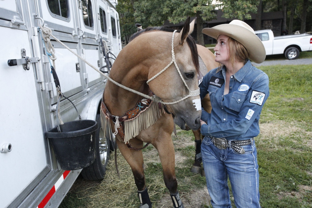 Tsunami nudges Taylor Young while she is listening to the announcer about a young male bull rider who was severely injured at Malibu Rodeo in Milford, Pennsylvania. (Kevin C. Downs/Agence Cosmos)