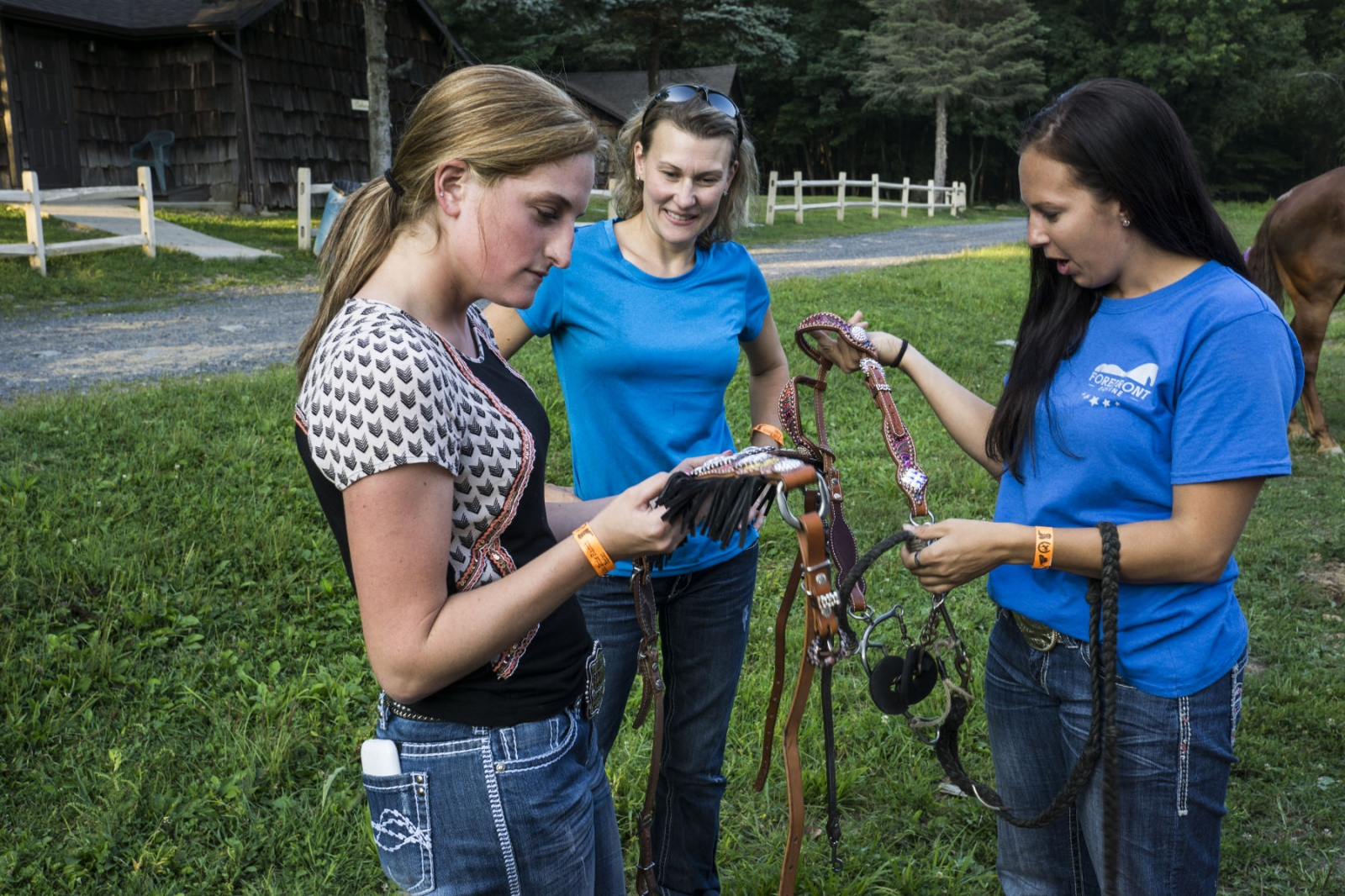 Taylor Young looking at decorated leather harnesses for horses, with friends from Cowtown Rodeo, at Malibu Rodeo in Milford, Pennsylvania. (Kevin C. Downs/Agence Cosmos)