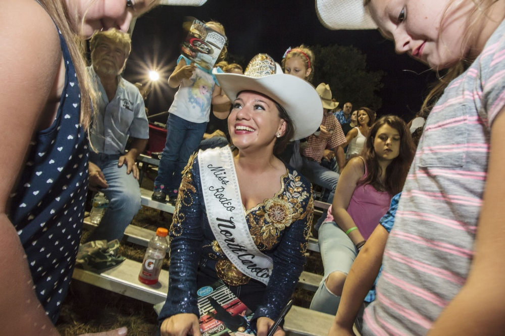 DEVIN REDDING in her Miss Rodeo uniform, with young fans at the 10th Annual Sandy Oaks Pro Rodeo in South Carolina. She is the 2015 Miss Rodeo North Carolina and First Lieutenant/ Finance Officer at Fort Bragg Special Forces Airborne. She spent three tours serving as a Finance Officer in both Fort Bragg and Kabul, Afghanistan. (August 22, 2015/Kevin C. Downs/Cosmos)