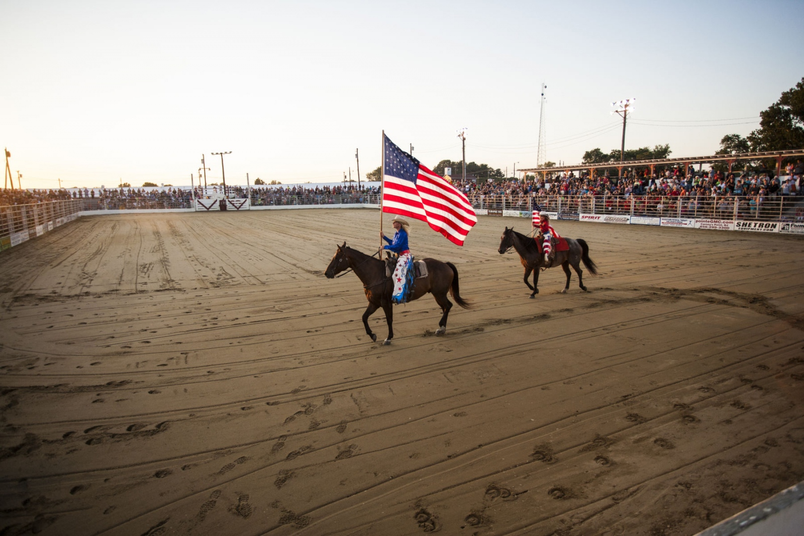 KatieHarris and hernicecarrying the American flag at Cowtown Rodeo in Woodstown, NJ. August 15, 2015 (Kevin C. Downs/Cosmos)