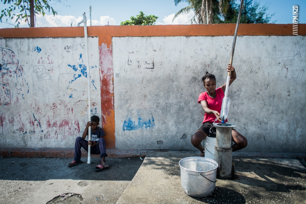 Photography image - A girl try to gets water in a faulty pump using a perch, savanna, Les cayes February 2017. Many of the communities in southern Haiti affected by Hurricane Matthew in October 2016 are still struggling to rise again.