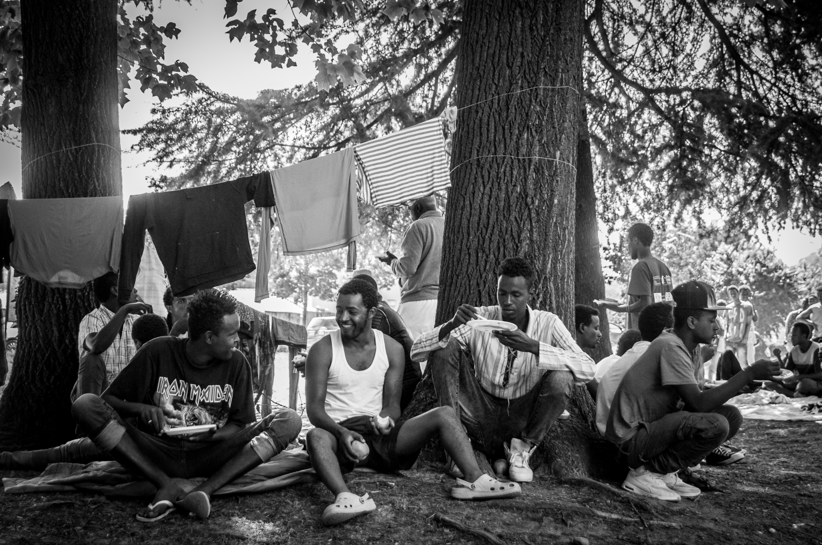 A group of migrants takes a break to dine among the tents at a temporary refugee camp.