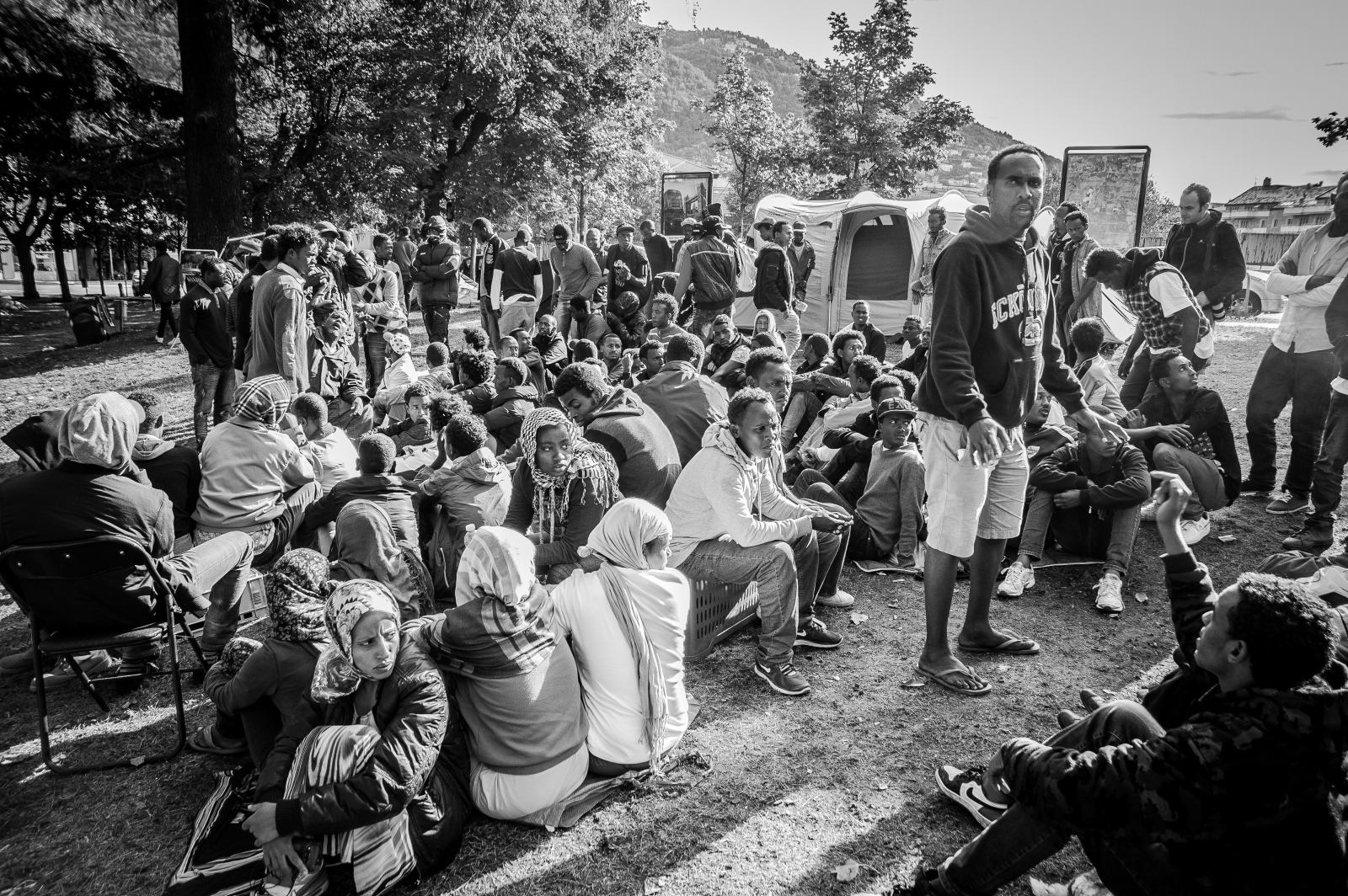 A large group of migrants waits for the opening of a refugee camp built by the Italian Red Cross.