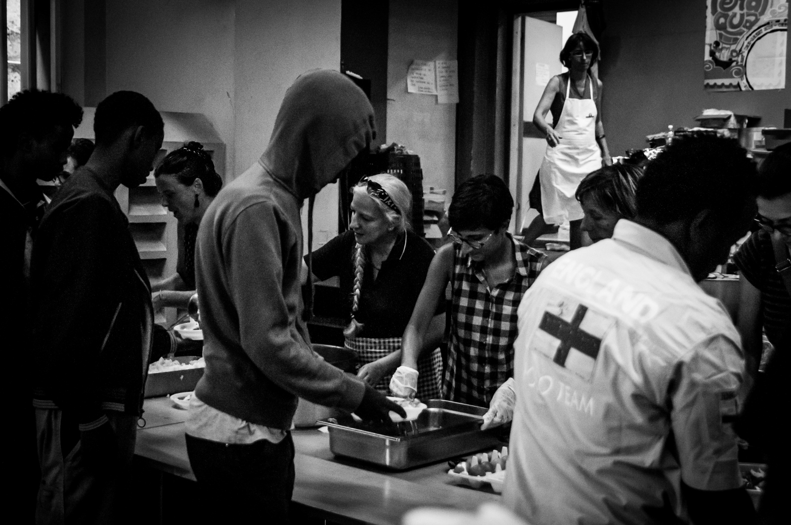 A group of migrants takes a dinner offered by Caritas volunteers in the soup kitchen. Caritas International is a confederation of 165 Catholic relief, development and social service organizations operating in over 200 countries and territories worldwide.
