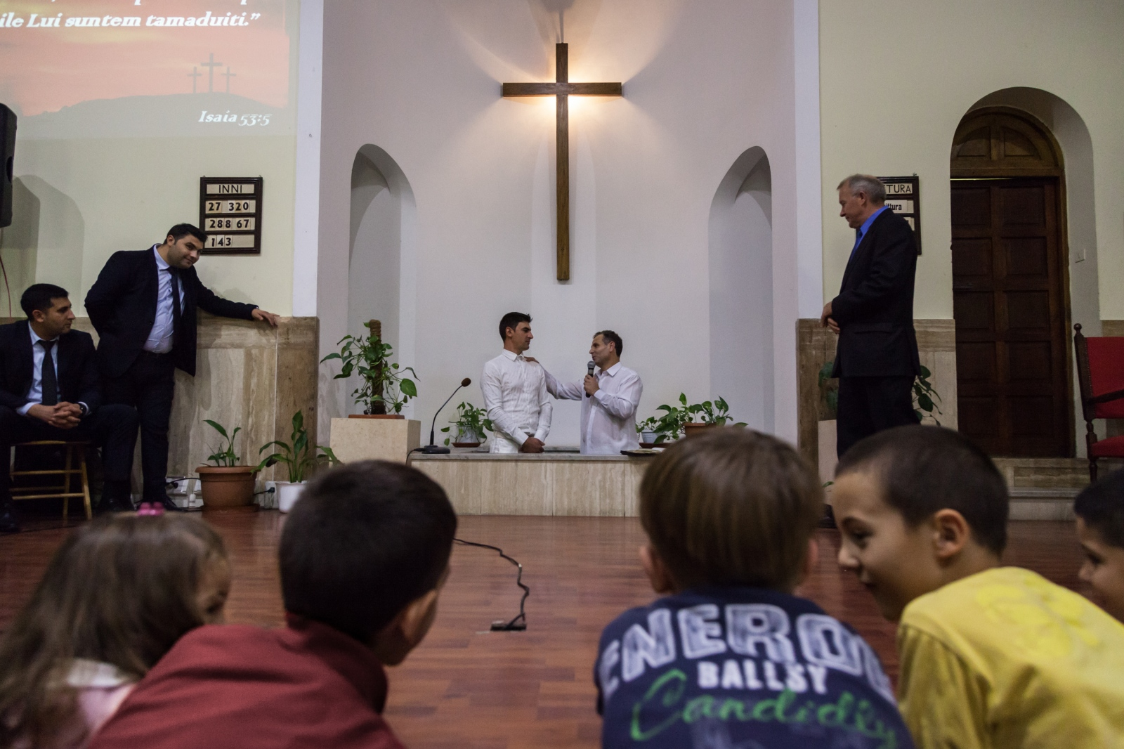 A young man from Romania, on the left, gets baptized in the Romanian Baptist Church of Centocelle, a working class neighborhood in southeast Rome.