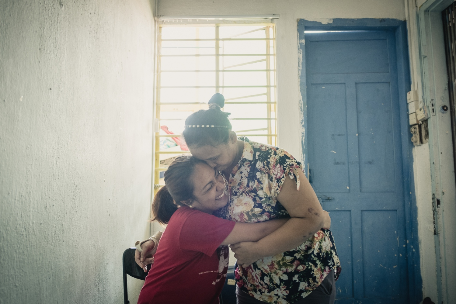 Singapore, 2016. Indonesian Nina Duwi Koriah, 29, is comforted by a friend at the HOME shelter in Singapore. Unhappy with the treatment from her employer after one week she sought help from her agent, who refused to transfer her to a new employer. One week later the agent agreed to take Nina in and brought her out of the employer's house. While housed at the home of her agent Nina reports the agent was displeased that she did not finish her contract and shouted at her. After three days of being locked in the agent's home, Nina opened a window with the intention to call for help or try and escape. She says she cannot remember what happened next but she woke up in the hospital. She had fallen from the third floor and broken her left elbow, right arm and wrist and right leg. She spent the rest of her time in Singapore under the care of local NGO, HOME. The Humanitarian Organisation for Migration Economics (HOME) is an organisation that provides direct assistance to men and women migrants and victims of human trafficking and forced labour.
