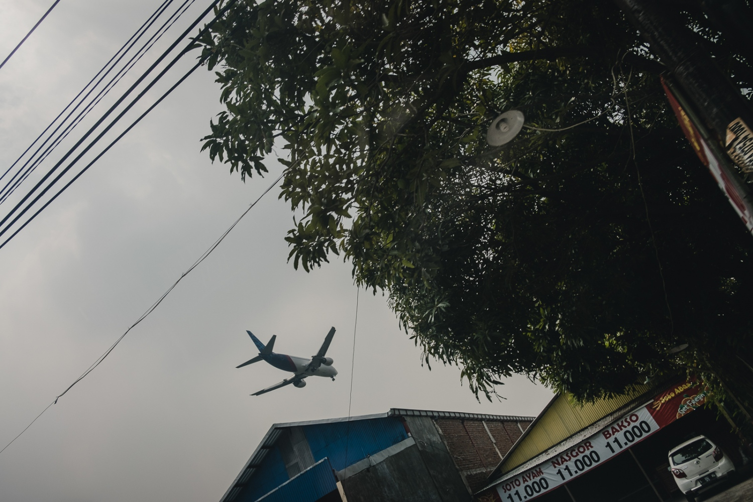 Indonesia, 2016. An aircraft flys over on approach to Surabaya Juanda International Airport, East Java.