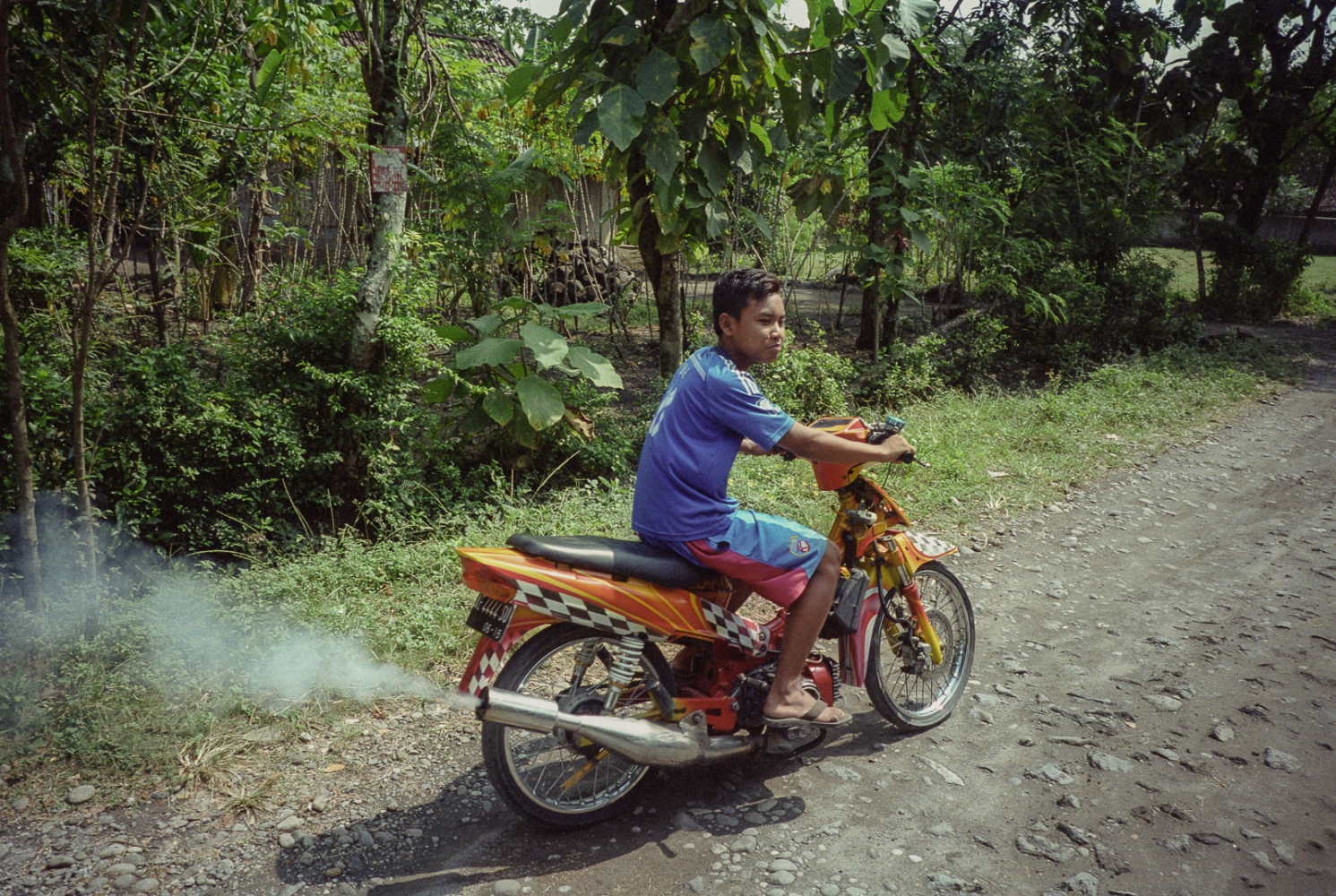 Indonesia, 2016. Mohammad Sultan Andri, 15 rides a motorcycle away from his family home in the village of Winong near the town of Ngawi, East Java. Mohammad's sister, Nina Duwi Koriah, lives here with her husband, her two children, her father and her two brothers. Now back in Indonesia after her accident in Singapore, where she was employed as a domestic worker, Nina is staying with her family until she is well enough to work. She intends to stay near home, and look for work in the town of Ngawi, possibly as a sales assistant.