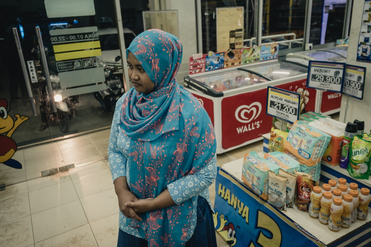 Indonesia, 2016. Indonesian Nina Duwi Koriah, 29, in a convenience store in Ngawi, East Java. Nina lives here with her husband, her two children, her father and her two brothers. Now back in Indonesia after her accident in Singapore, where she was employed as a domestic worker, she is staying with her family until she is well enough to work. She intends to stay near home, and look for work in the town of Ngawi, possibly as a sales assistant.