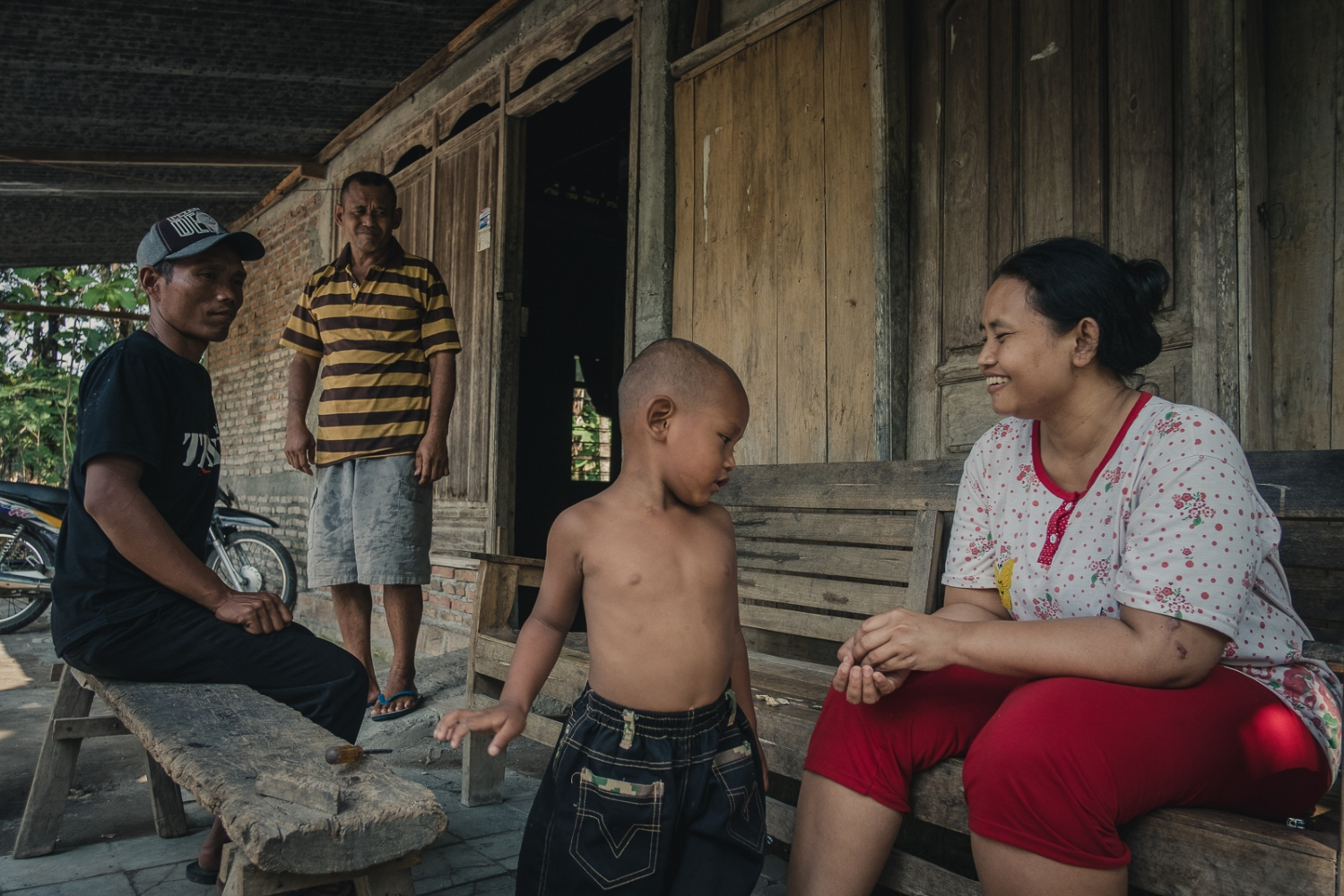 Indonesia, 2016. (From Left) Mansyur, 39 and his father in law Mukshin, 55 look on as the 4 year old son of Mansyur, Safa Mustajab plays with his mother Nina Duwi Koriah, 29 in their family home in the village of Winong near the town of Ngawi, East Java. Nina lives here with her husband, her two children, her father and her two brothers.