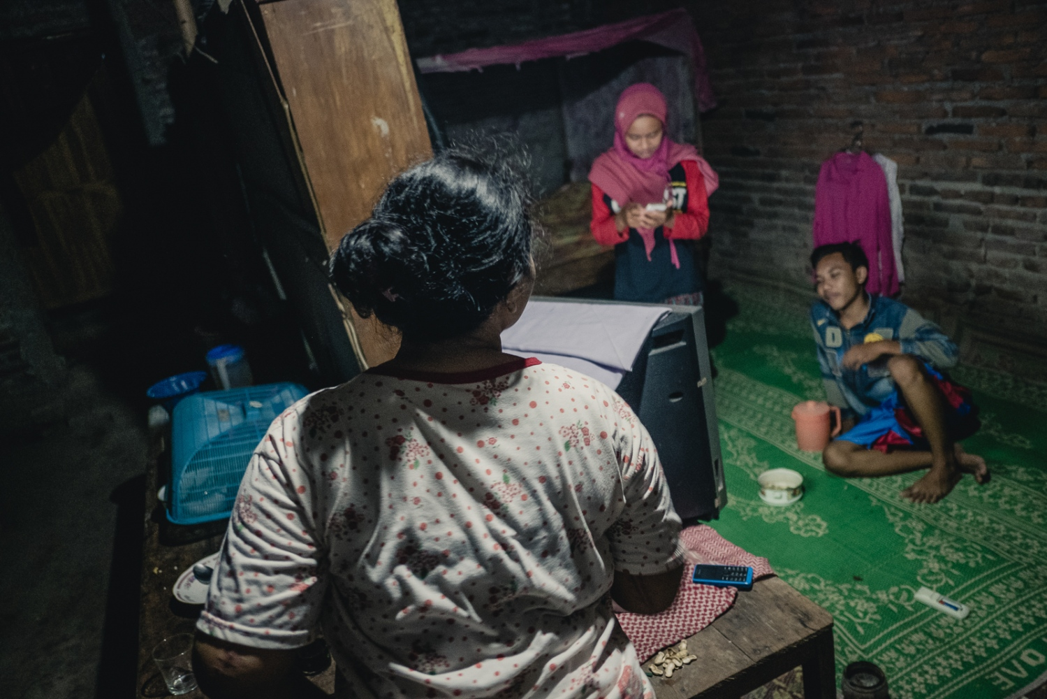 Indonesia, 2016. Nina Duwi Koriah, 29 with her brother Mohammad Sultan Andri, 15 and her daughter Mahmudah Ayu Ashari, 13 in her family home in the village of Winong near the town of Ngawi, East Java. Nina lives here with her husband, her two children, her father and her two brothers.
