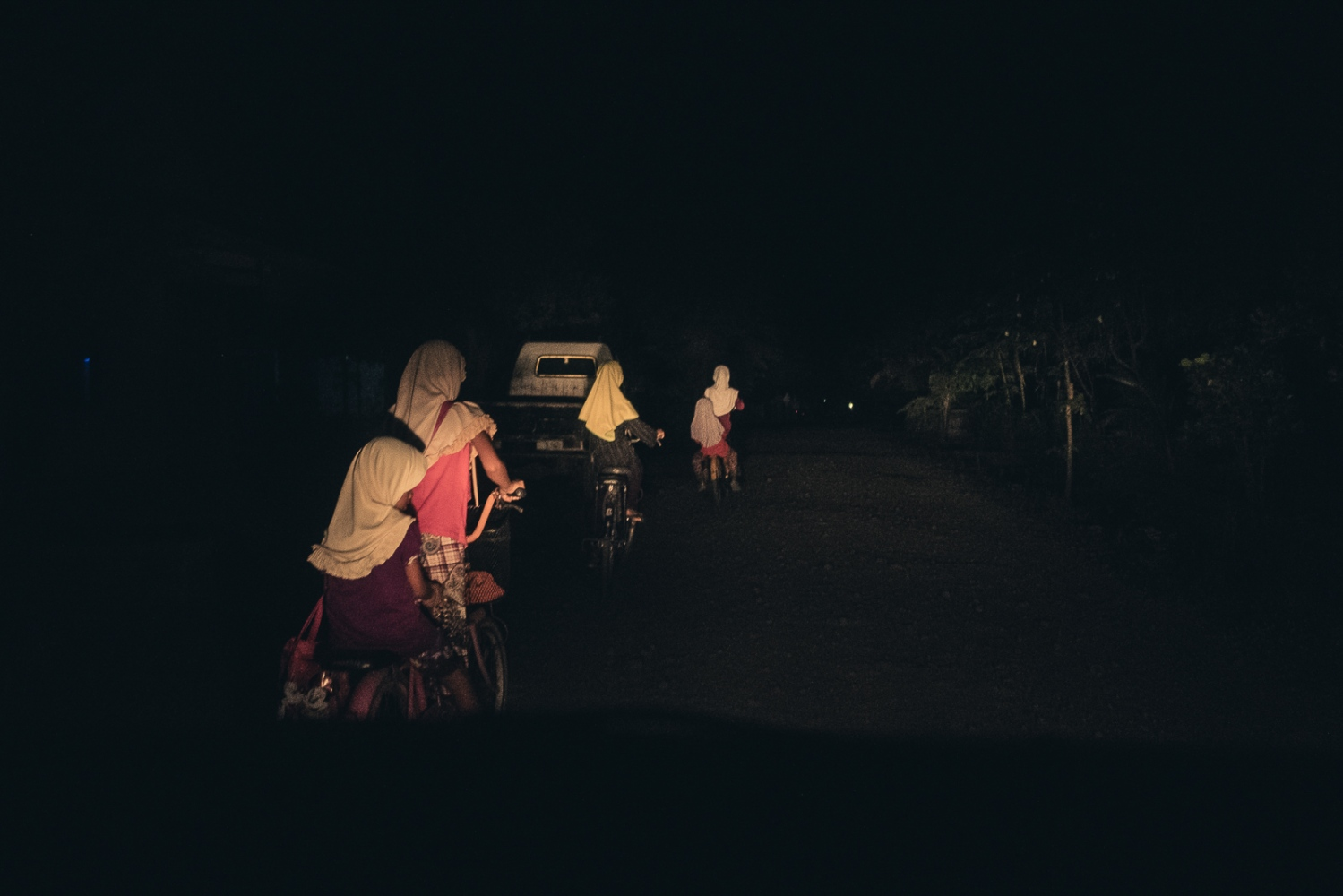 Indonesia, 2016. Young girls cycle in the dark along a road linking the town of Ngawi in East Java to surrounding villages.