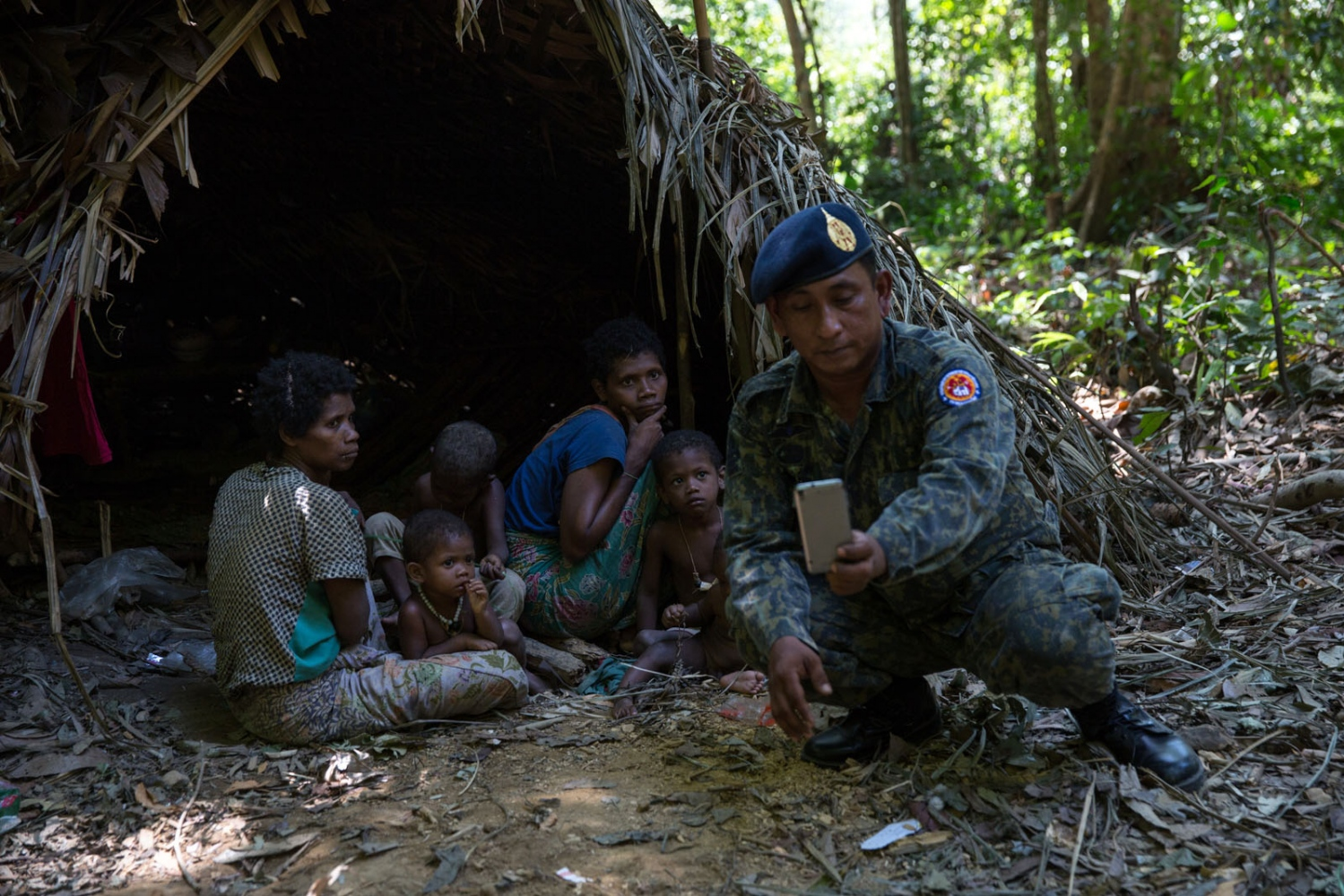 A Thai soldier takes a selfie with a group of Maniq women and children. This group has built its settlement close to a river that is frequently visited by tourists. Tourists regularly visit them taking selfies and photos much to the disliking of the Maniq, but timid and shy they rarely say no. Satun - March 2017