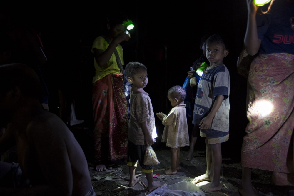 A group of Maniq children and their mothers use head-torches in their camp at night. Satun - September 2017