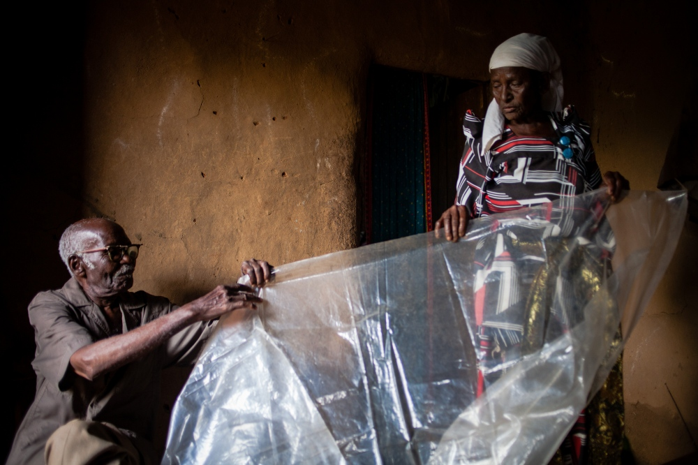 Masa with help from her 90 year old husband unfolds the plastic sheet she uses during deliveries at their home in Bududa, Uganda.