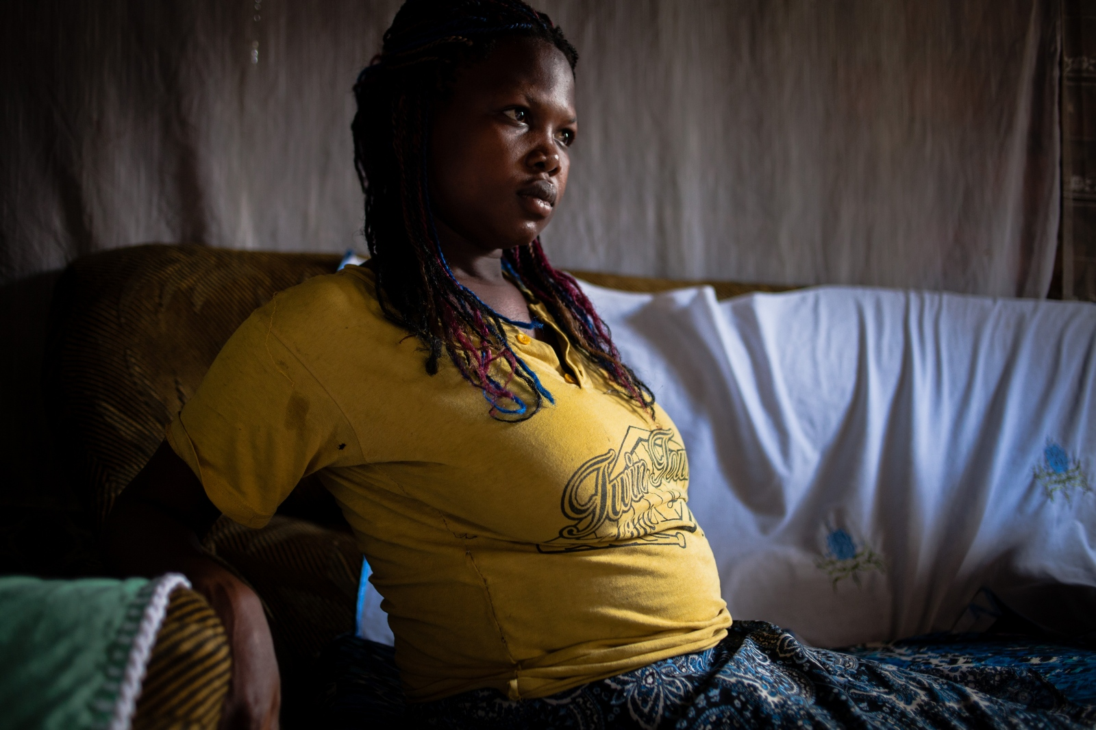 A pregnant woman relaxes in the TBA's house after a check-up in Bududa District, Uganda. Women visit the TBAs' home as they would a hospital for scheduled appointments.