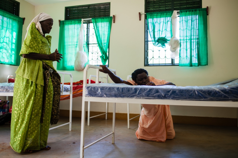 Masa comforts her patient during the worst of her labor pains at the new health center in Bududa, Uganda. Masa's presence and support gives her patient the confidence to adopt and appreciate the access to modern health services.
