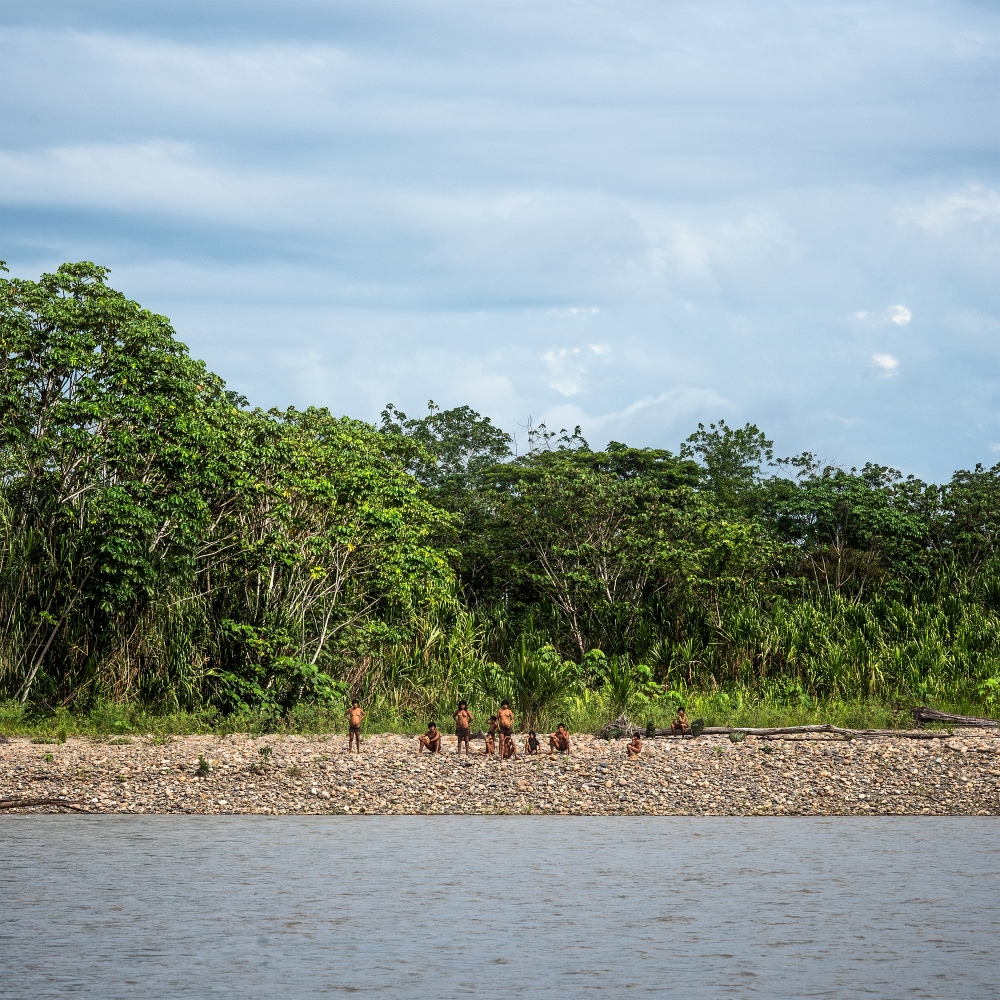 Members of the isolated Mashco-Piro tribe wait on the beach for the Peruvian protection agents from the Namole outpost to make contact on the Madre De Dios River.