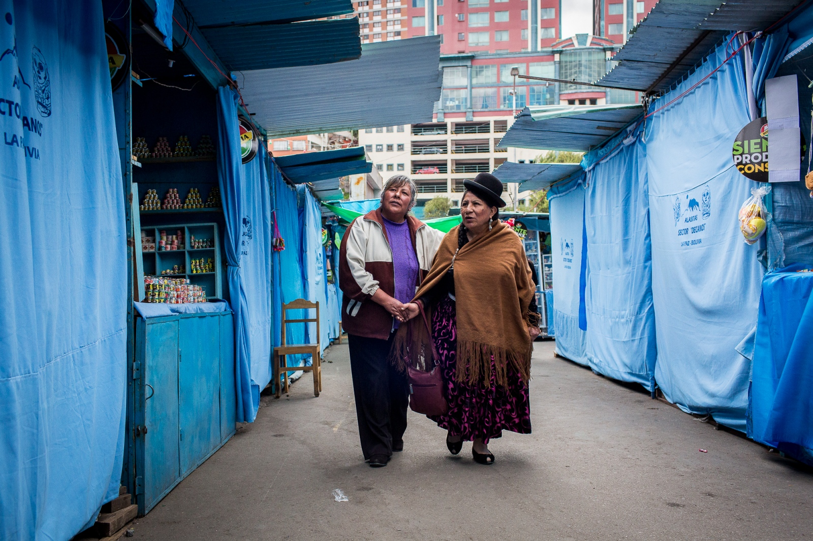 Remedios Loza walks with an admirer through an alley of the Alasitas handicraft market, La Paz. Comadre Remedios as Loza is known is revered by other women and consider a pioneer for indigenous women rights.
