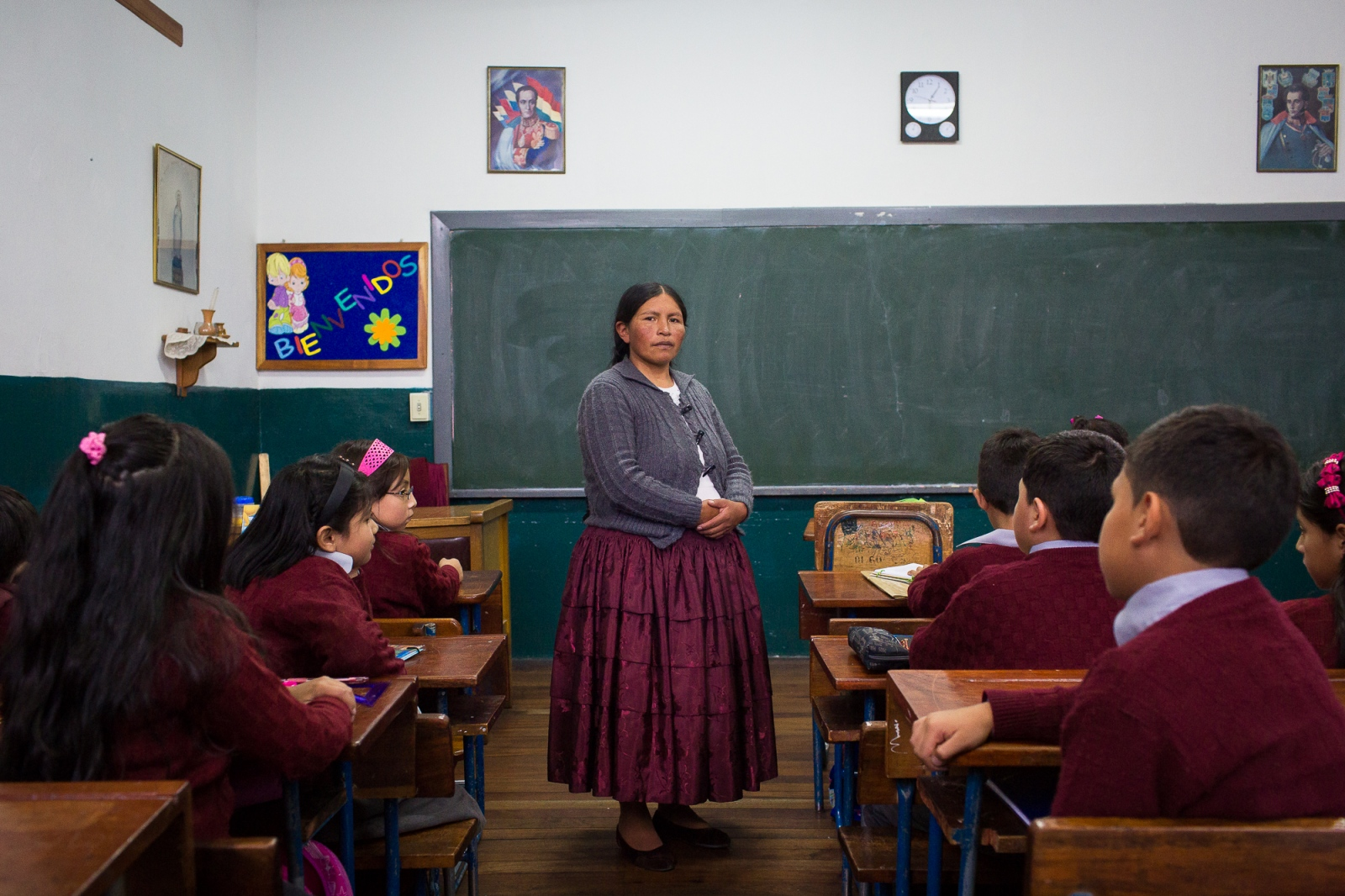 "Celia Laura in her classroom at San Calixto Private School, La Paz. Since 2013, students in Bolivia have had to learn Spanish, English, and one of the native languages—such as Aymara or Quechua. Professor Laura, who teaches Aymara, was the first indigenous woman in the country to become a teacher in a private school. There was once a time when ""cholitas"" were not allowed to study in schools unless they swapped their traditional clothing for Westernized garb."