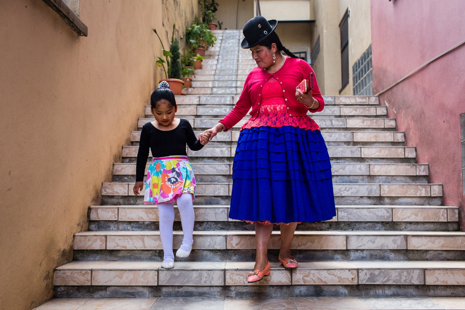 "Celia Ramos walks with her daughter after a ballet class in La Paz. Celia works to the same family house since she was 14. She says that her boss gave her a life that she couldn't dream, by letting her study and giving her a more comfortable life and she thanks her boss for it to the point to call it ""Mom"". But she dreams of bigger opportunities to her daughter and is making everything possible for her to get it, like make her study in a good school, dance ballet and learn chess."