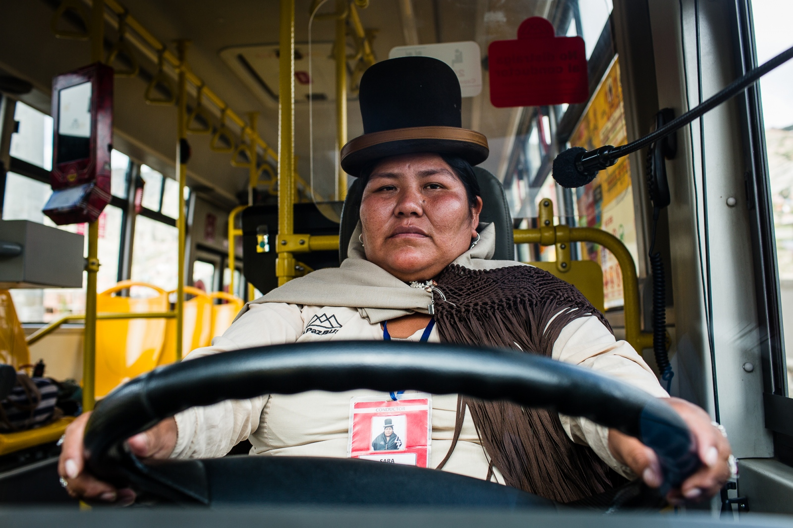 "Sara Mamani on the wheel of the bus that she drives daily through the streets of La Paz. Sara is the second ""cholita"" to ever drive a bus in La Paz. She started to drive first small vans with passengers as a way to make money to feed her children after the separation from her partner, then she went to drive bigger buses. Sara loves it so much that wishes to become an international truck driver; she is just waiting for her children to grow up so she can follow her dream."