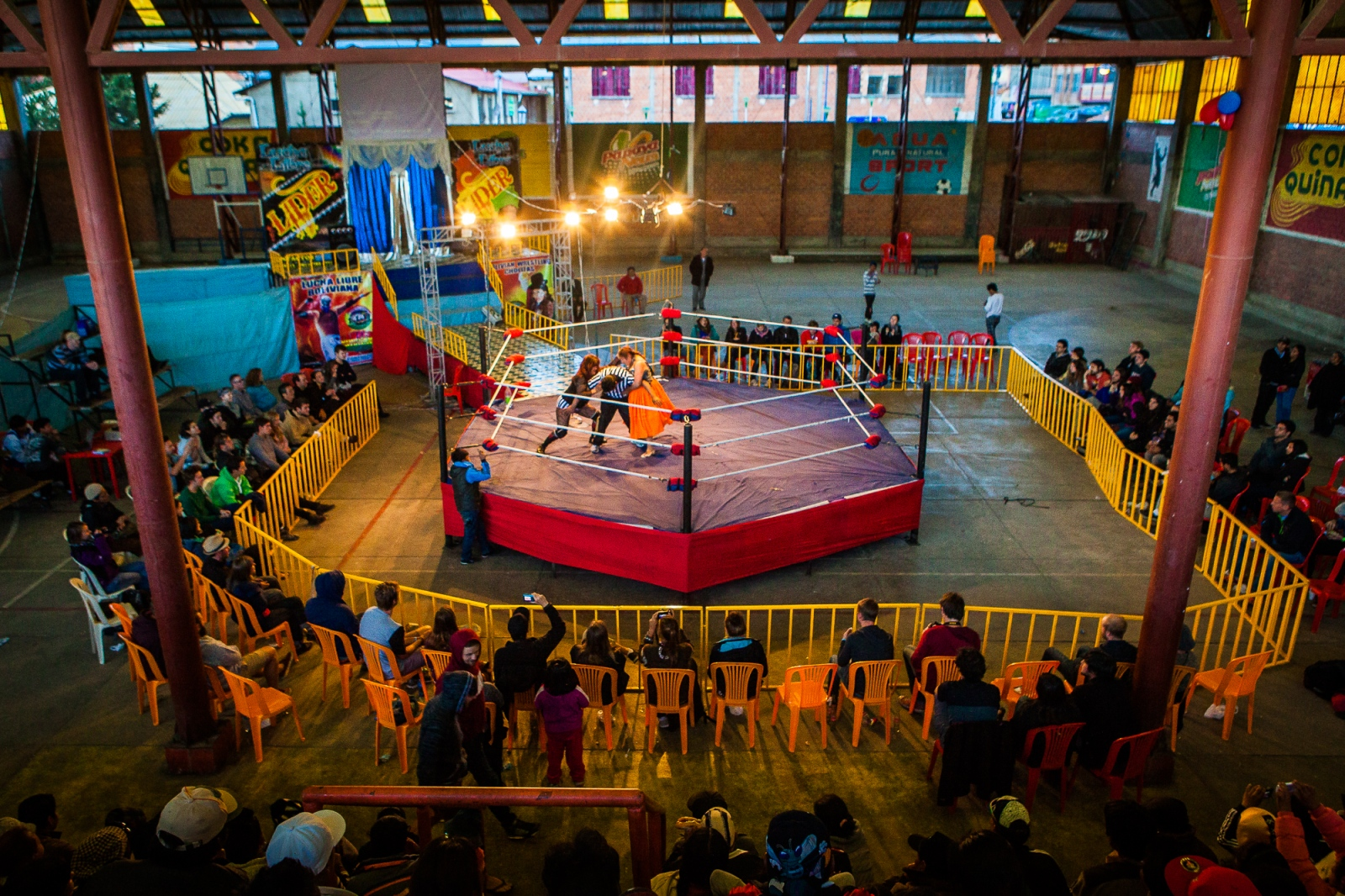 A team of cholitas wrestle in El Alto's sports complex. In July 2014, a group of cholitas decided to form their own wrestling association and organize their own events—despite Bolivian mainstream culture's tendency to enforce a rigid understanding of traditional gender roles. Many of these women have found that their male romantic partners were threatened by female strength; but that doesn't stop these women from doing what they love.