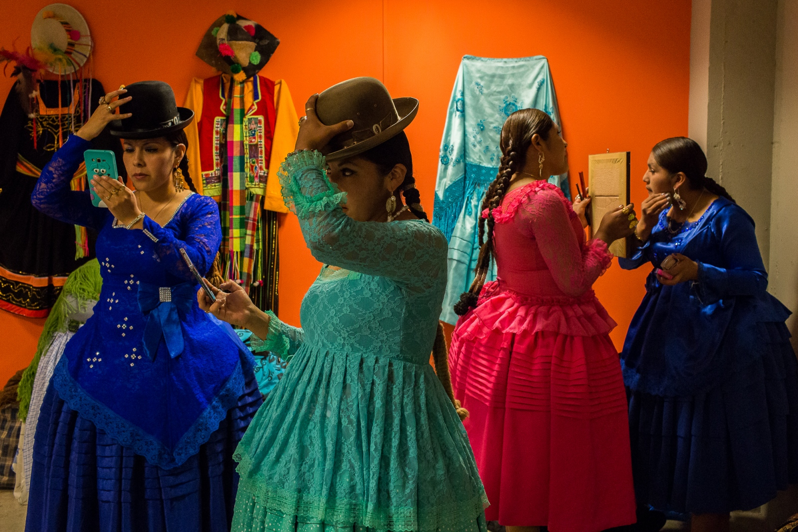 Cholitas prepare themselves backstage before ascending the catwalk at a fashion show in El Alto.