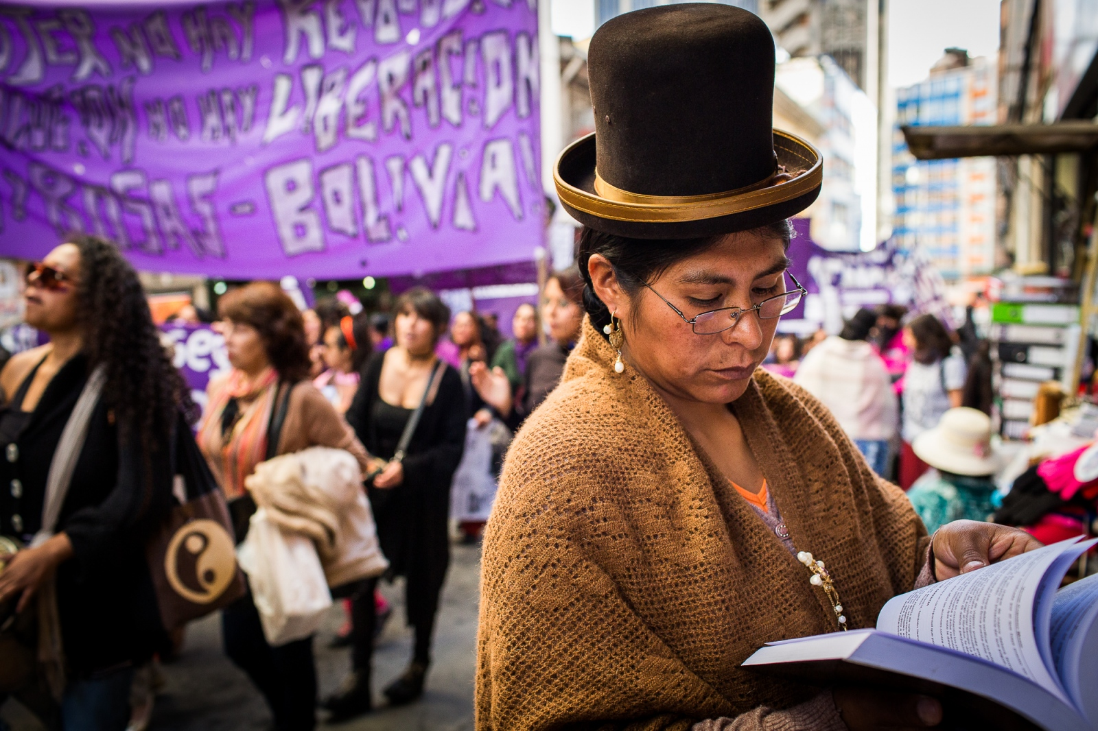 "A ""cholita"" reads a book next to a newsstand during an International Women Day march in La Paz. Despite all the progress women have made over the last decade, the fact remains that women—and especially indigenous women—are far from equal in Bolivian society. Issues like domestic violence and access to education are still major problems that will require further investment and dedication from Bolivia's government as well as from society at large."