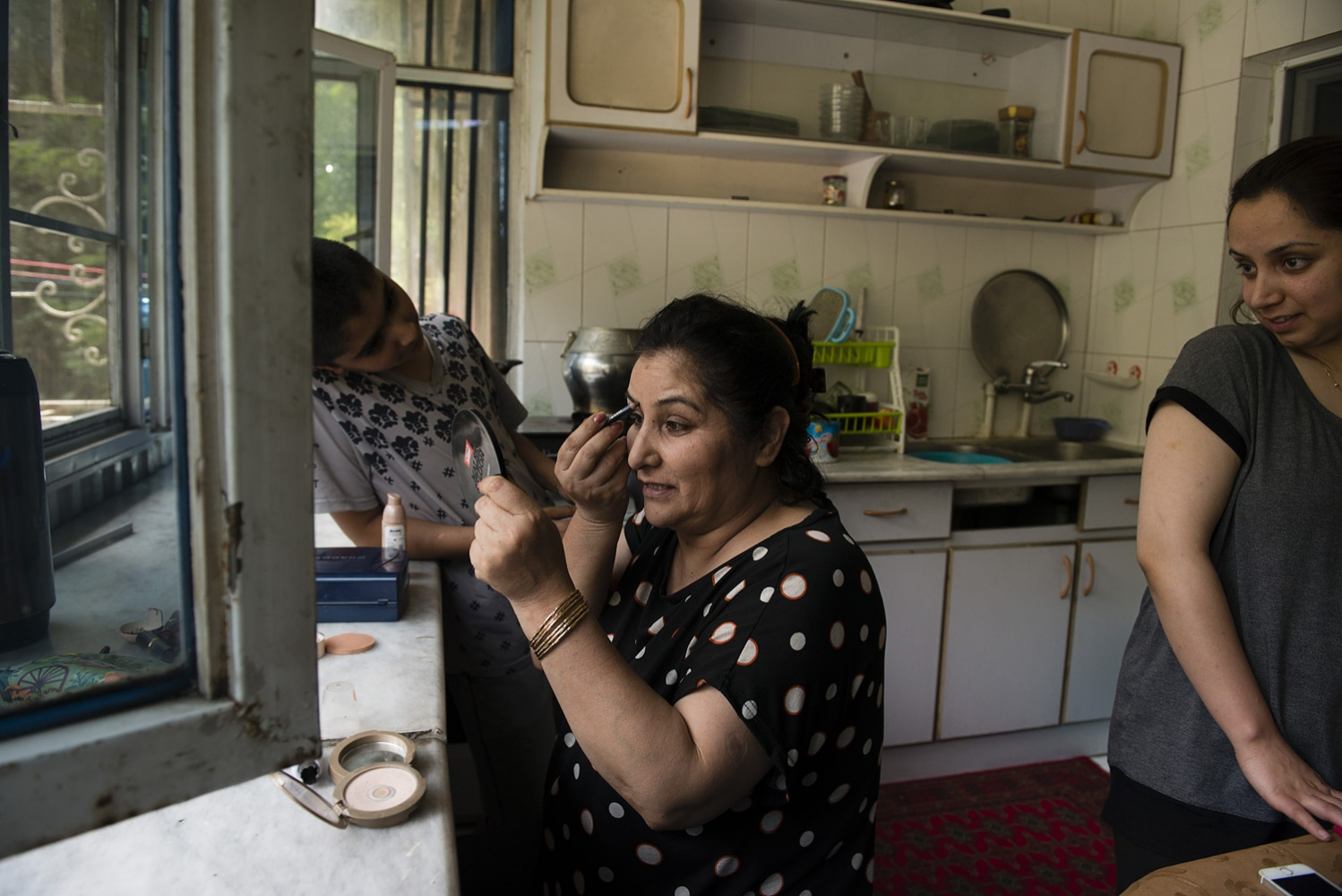 KABUL, AFGHANISTAN | 2016-08-26 | Aziza (52) puts on make up to get ready to go out after lunch. Aziza lost her husband to cancer in 2006 and brought up her 4 children on her own with the support of her brother-in-law, a prominent Afghan-Australian musician. She was never forced to remarry but temporarily lived with her brother-in-law's family in the same apartment, which she recalls to be the most difficult time. She works at the National TV and Radio of Afghanistan.