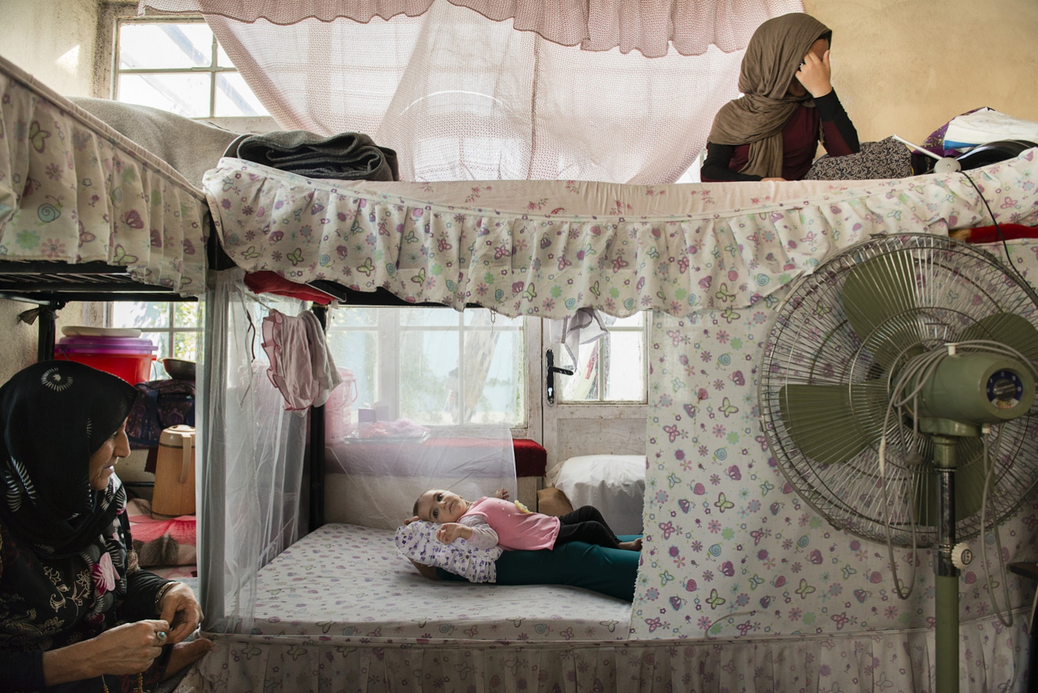 HERAT, AFGHANISTAN | 2016-09-04 | Wahida (20), who chose not to reveal her face, sits behind the curtain on her bed inside the female ward of Herat Prison. She was arrested when she was 7 months pregnant, convicted for helping her sister-in-law to murder her husband. Her daughter, Mahtab (10-month-old) was born inside the prison. Her biggest fear is the future when her sentence is over and she has to face the outside world on her own.